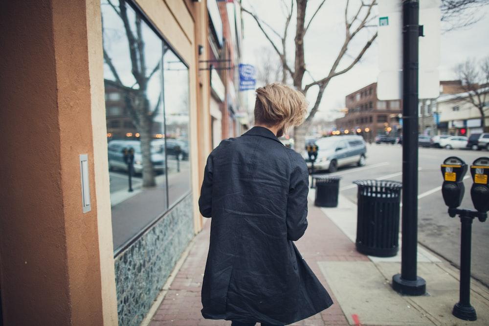person walking beside street at daytime