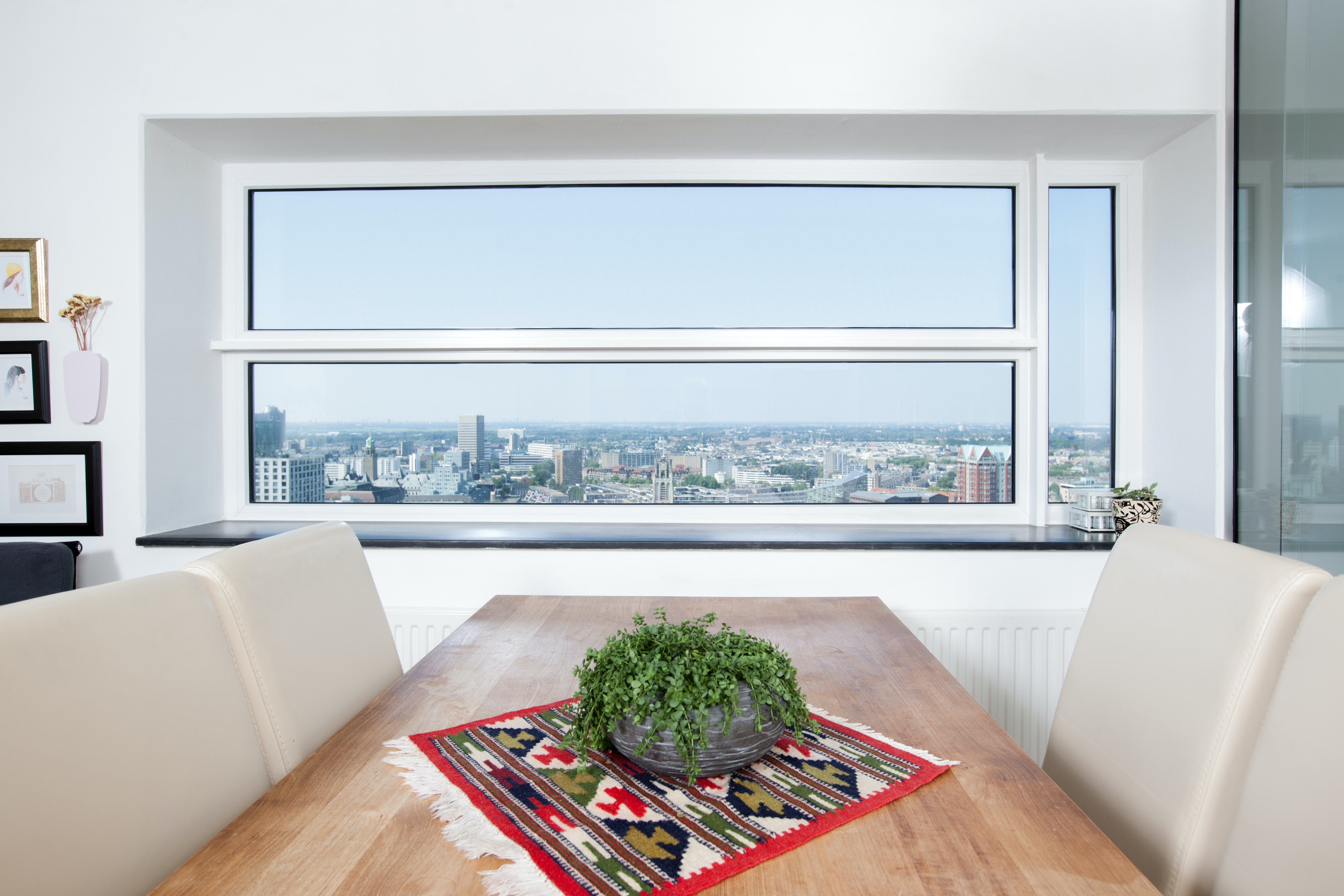 A potted plant on a table in a room with a wide window looking out on the city