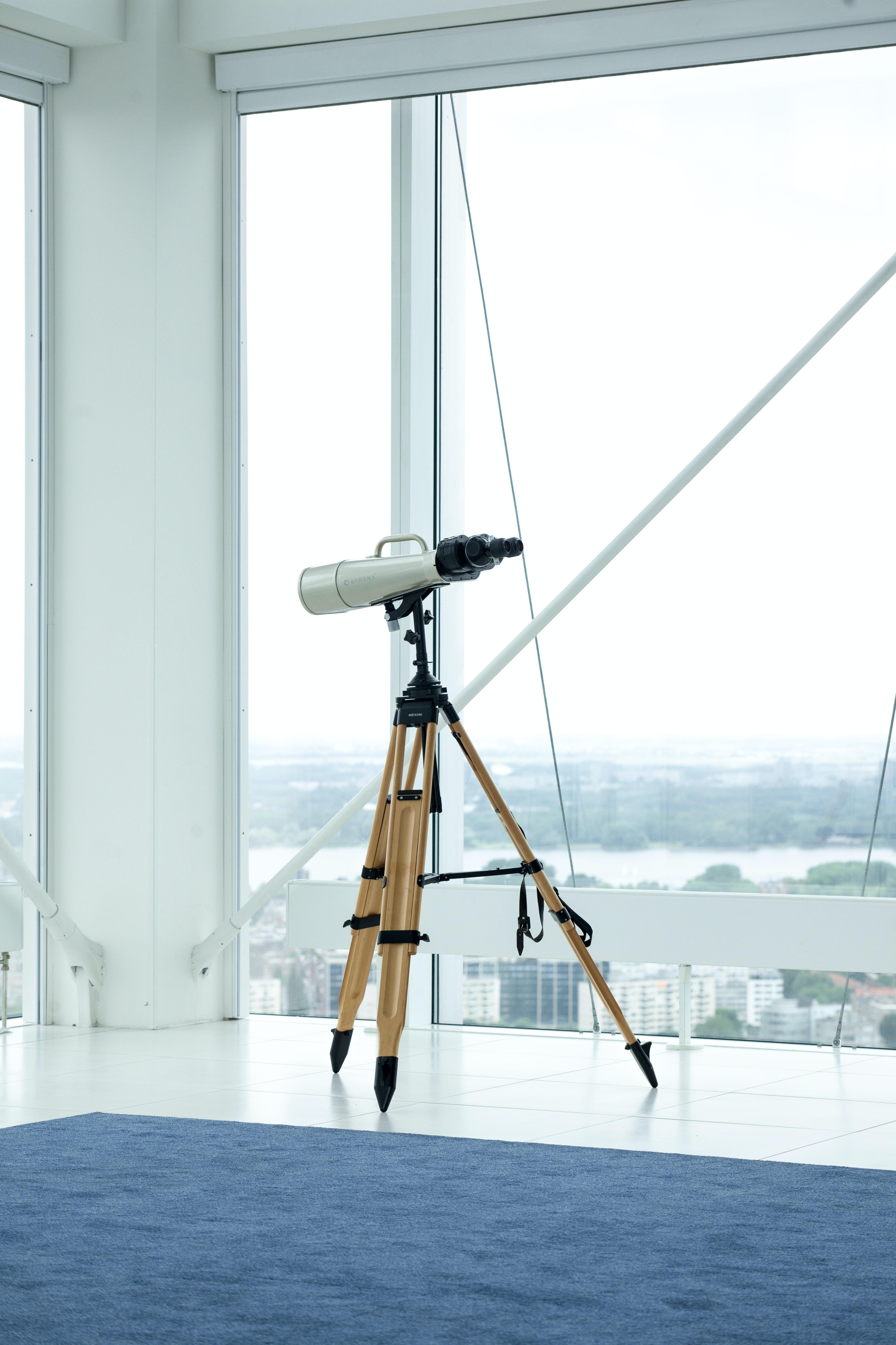 silver telescope beside glass window