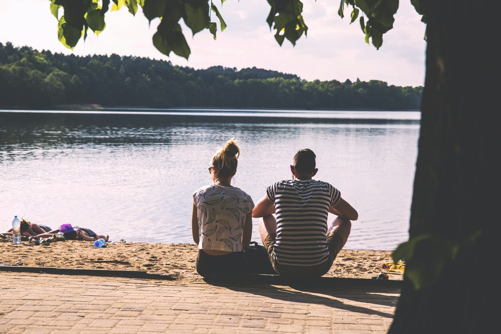 men and woman sitting on pavement facing body of water