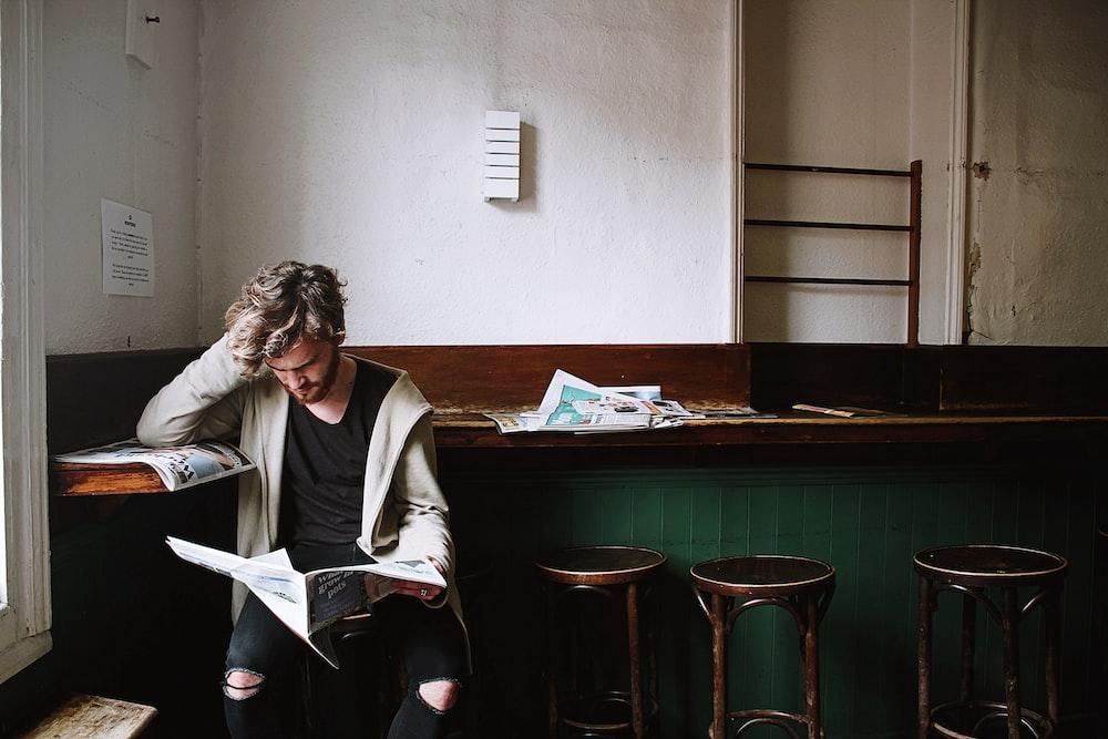 man sitting on bar stool while holding newspaper