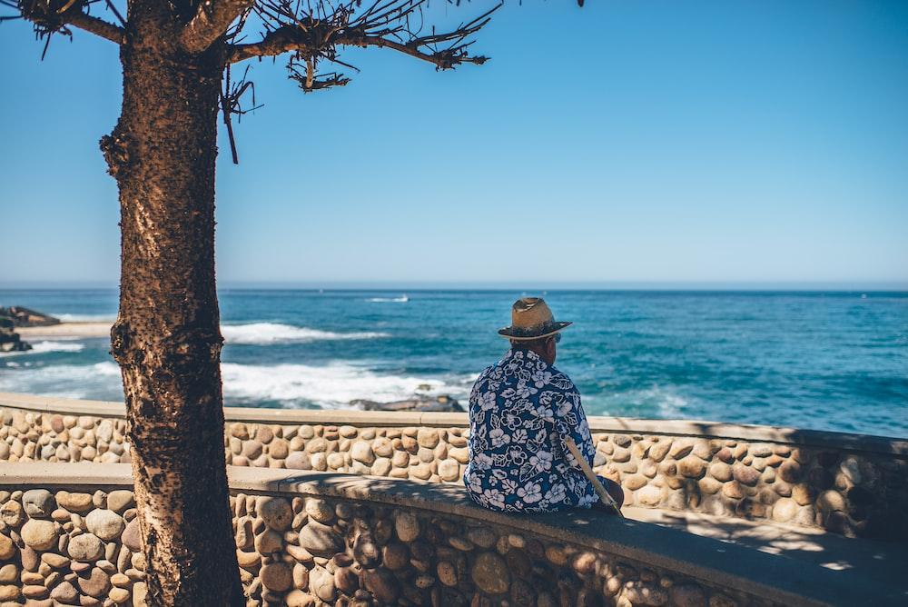 man sitting facing sea