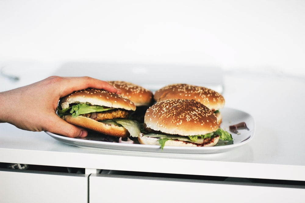 person holding hamburger on plate