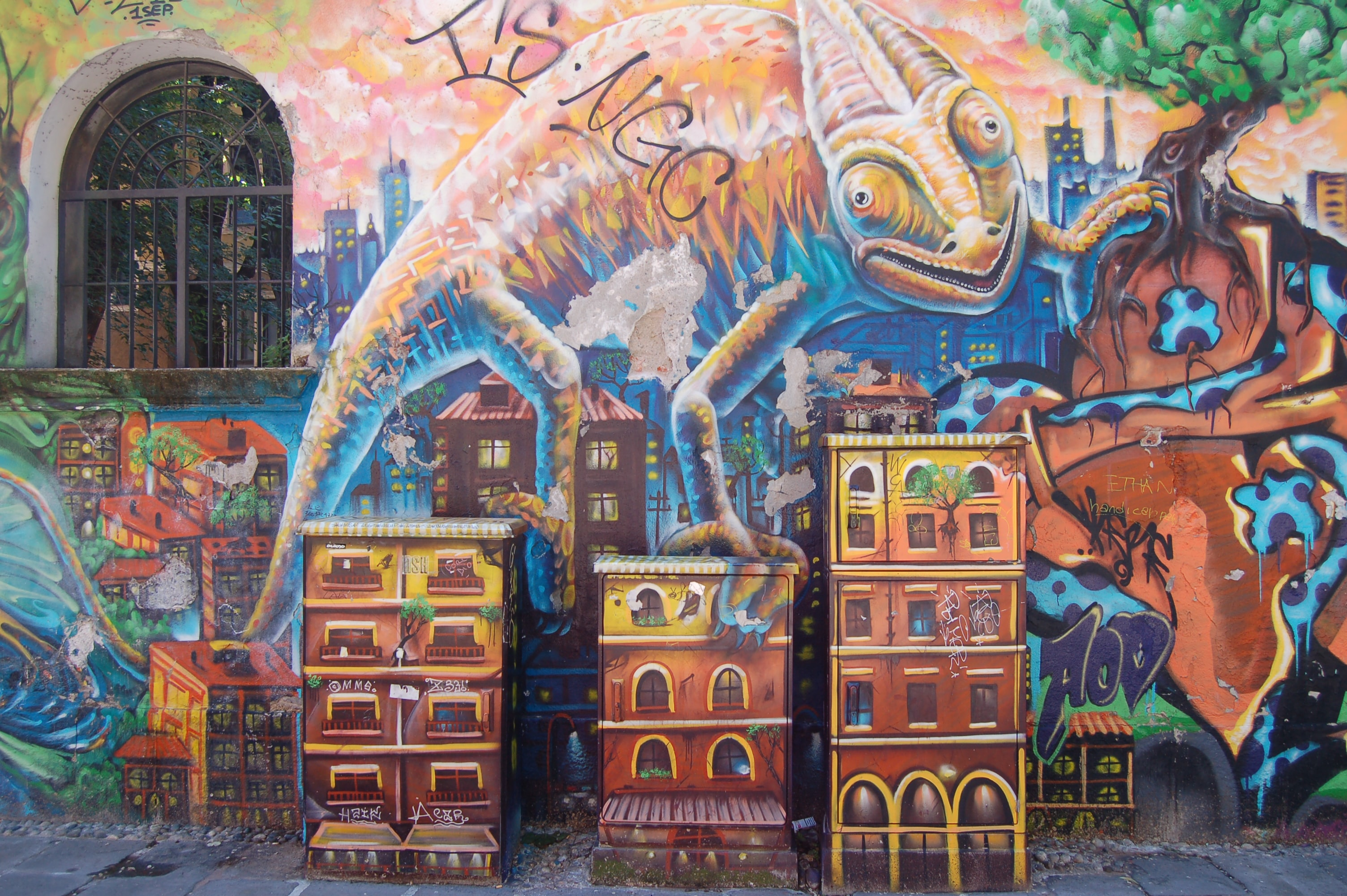 A wall mural of an oversized gecko climbing over tall city buildings.