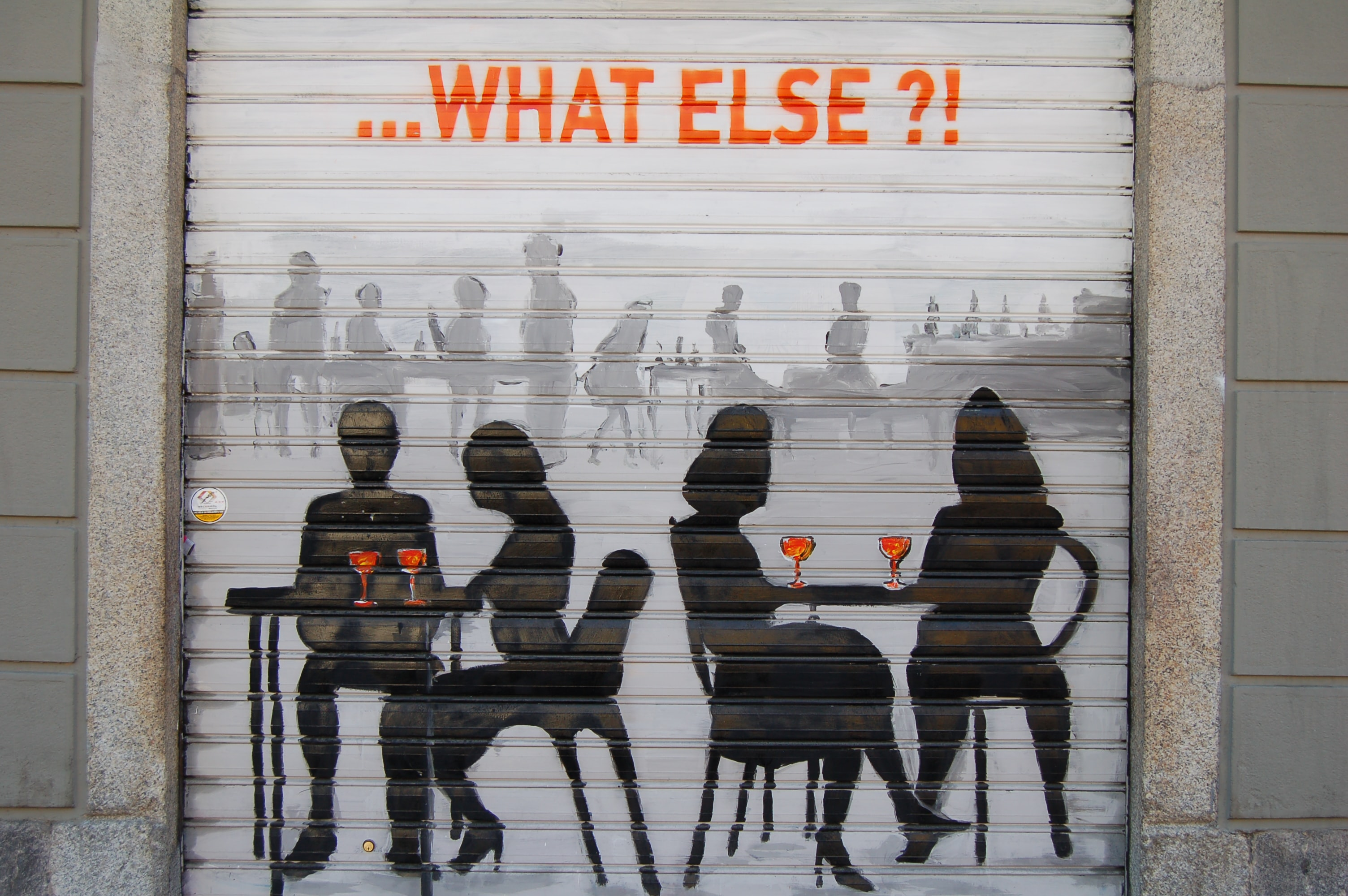 "A wall painting of two couples sitting and enjoying a glass of wine, with a title above in orange writing that says, ""...What else?!"""