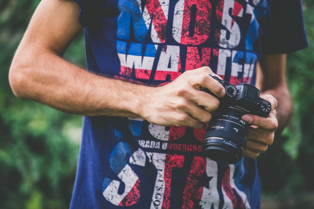 man in blue shirt holding DSLR camera