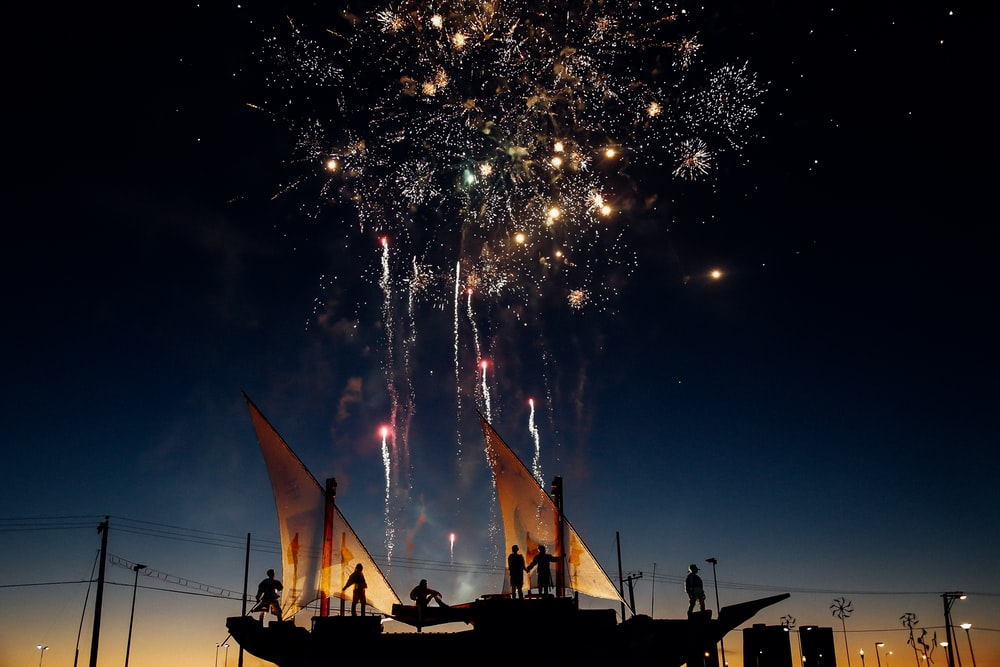 silhouette photography of person standing while watching fireworks in the sky