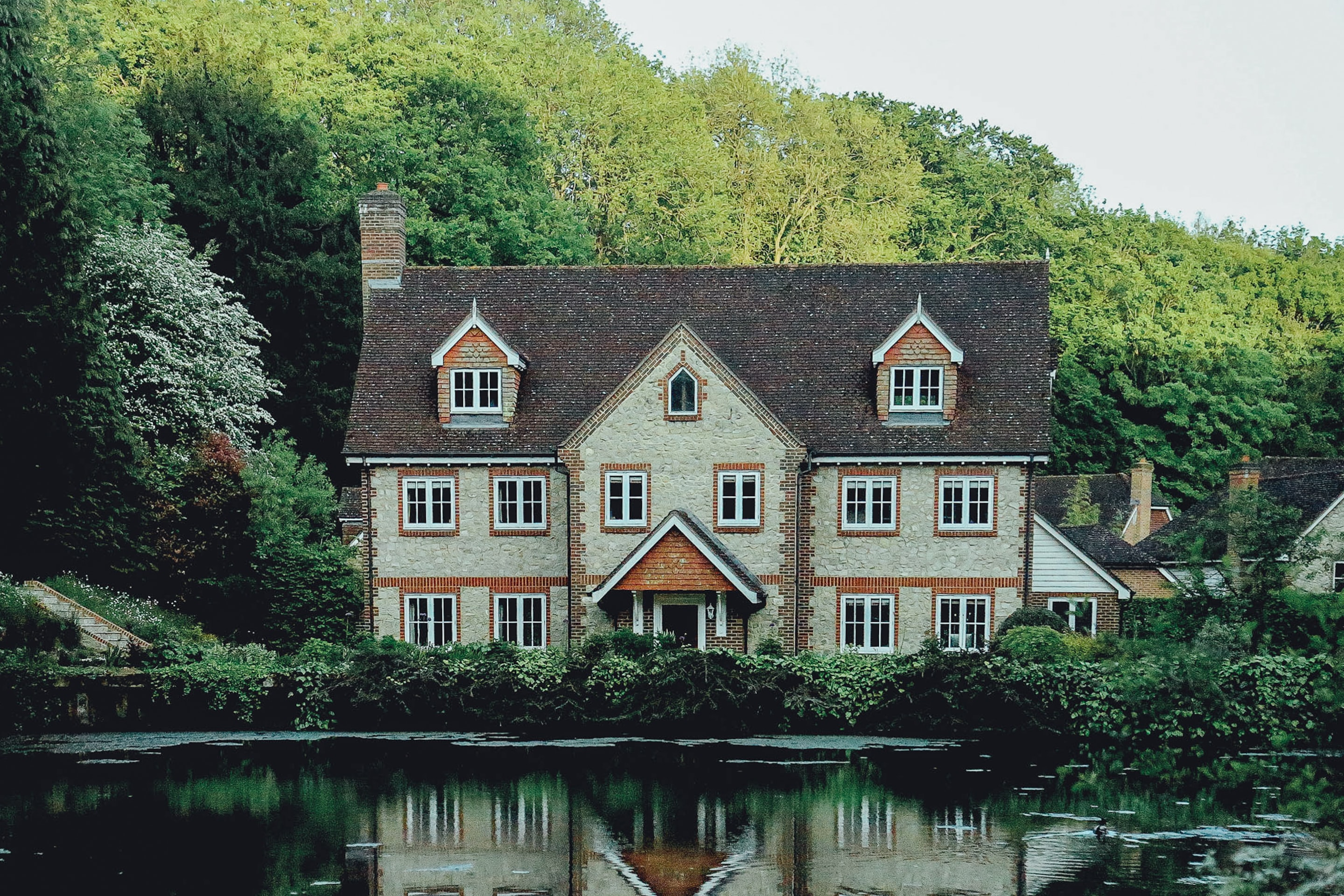 Elegant house in London next to a pond and in front of a forested hill