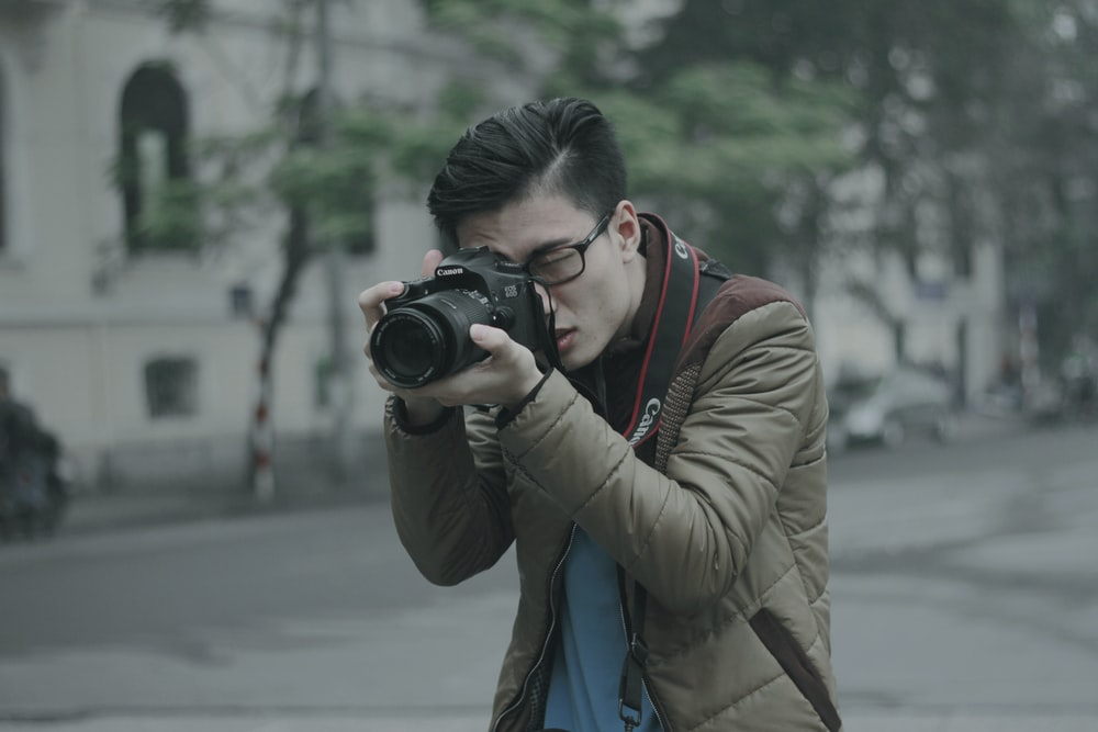 shallow focus photography of man taking photograph holding his camera