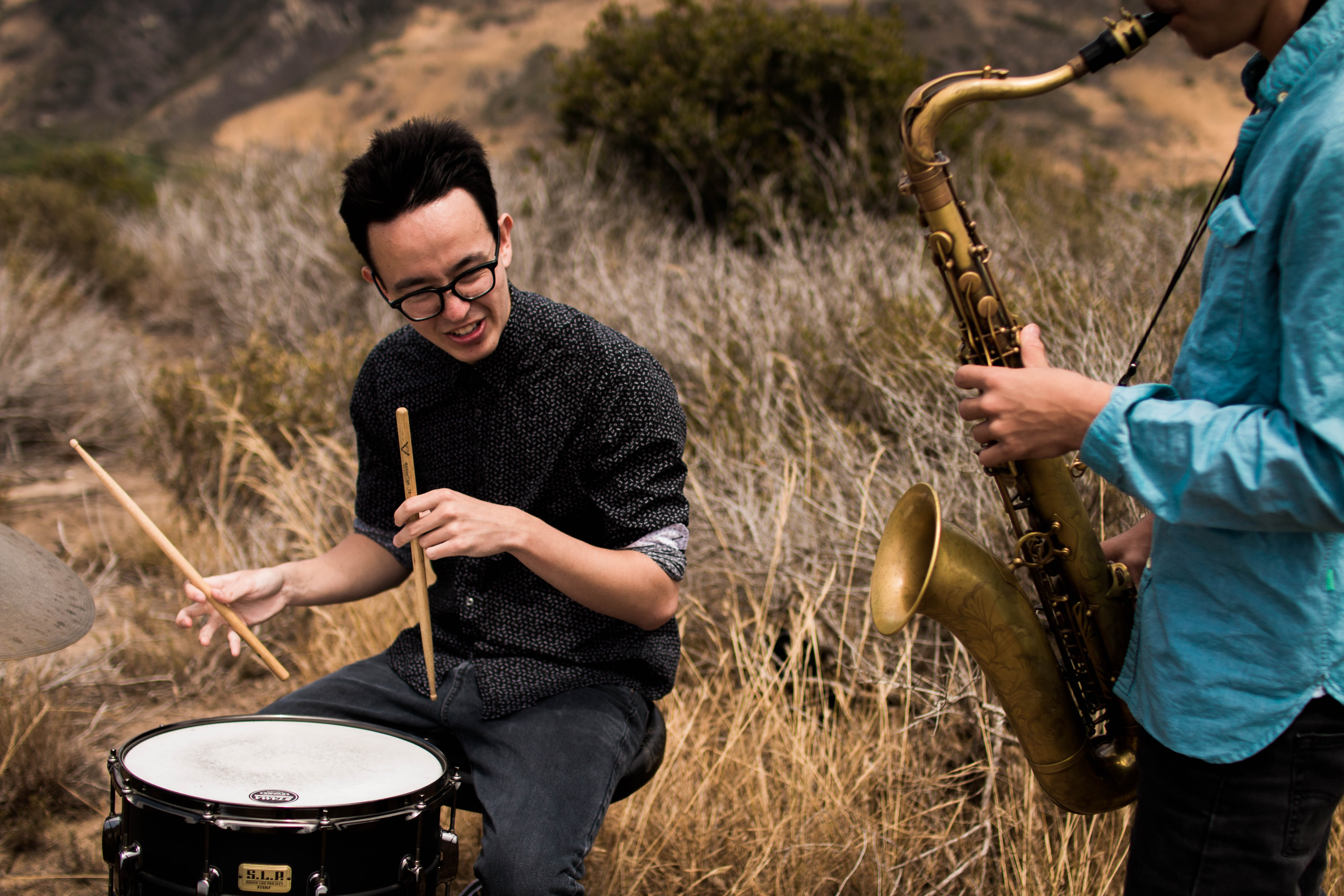 Two young men playing a drum and a saxophone in dry grass