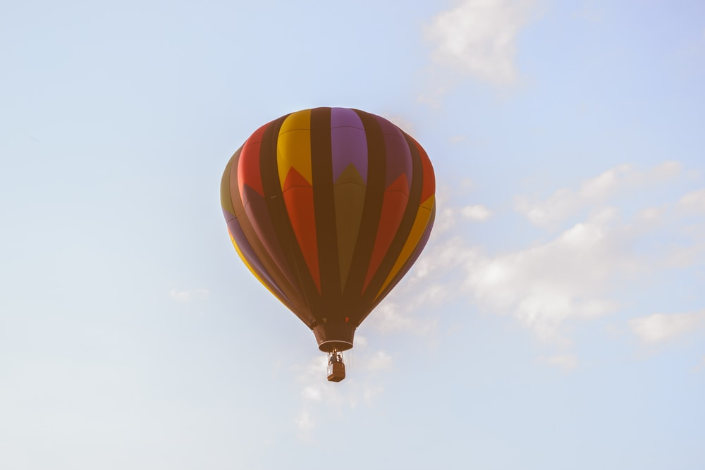 low angle photo of red and black hot air ballon
