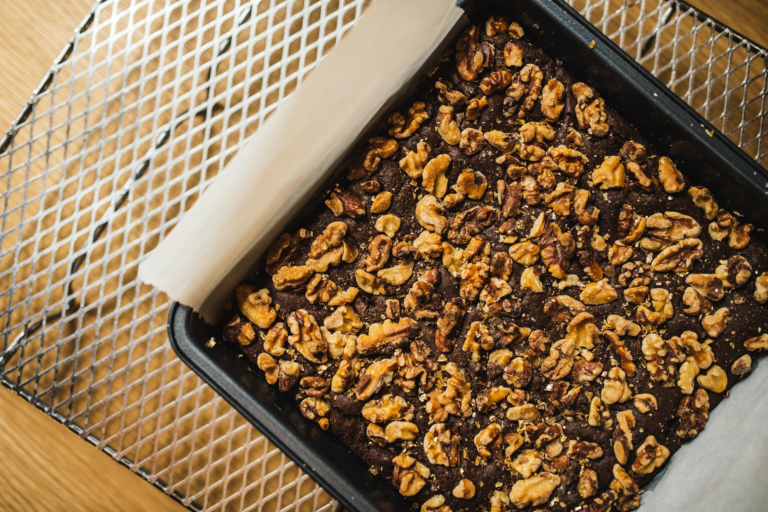 square brown nut cake on black baking pan
