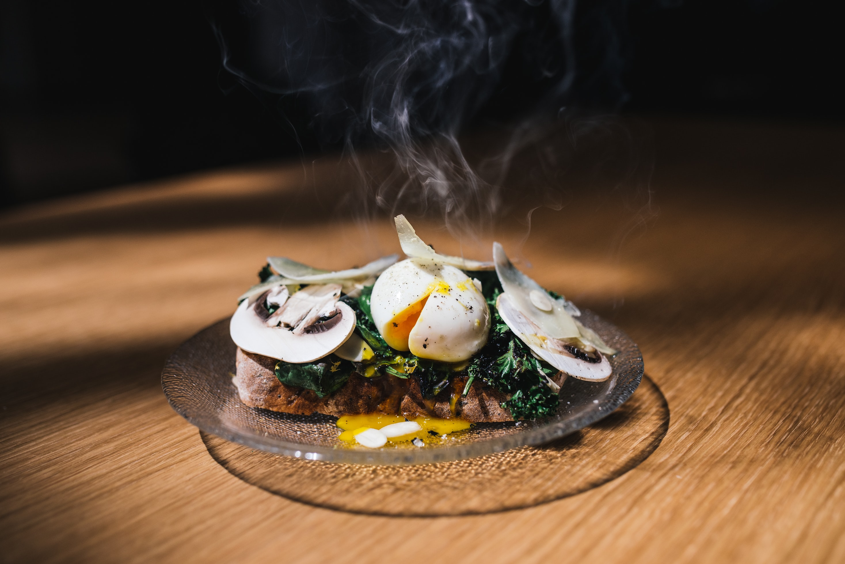 Gourmet cafe toast with a steaming poached egg, mushrooms, and greens