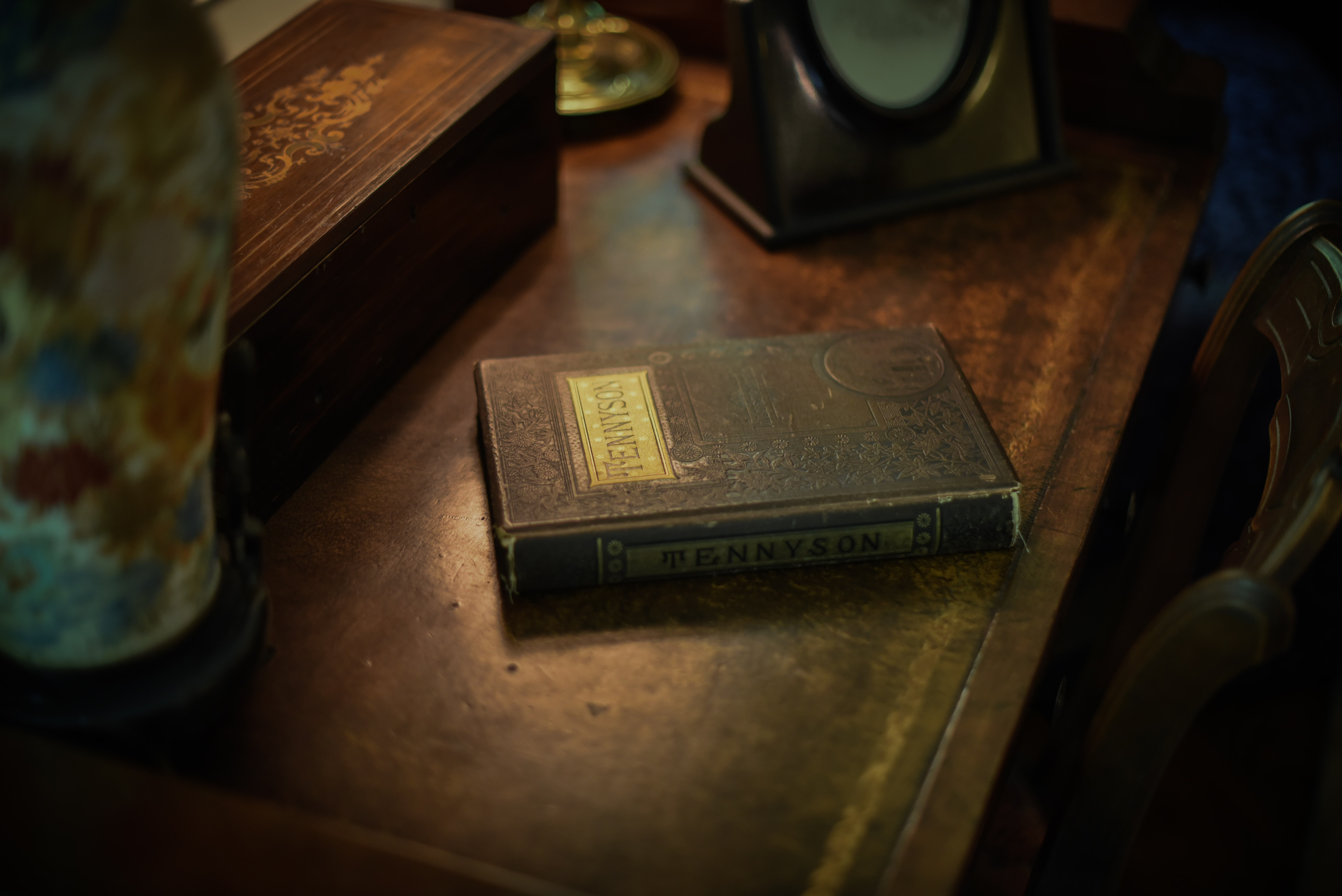 """An old, weathered book with """"Tennyson"""" on the spine and cover sits on a wooden dresser"""