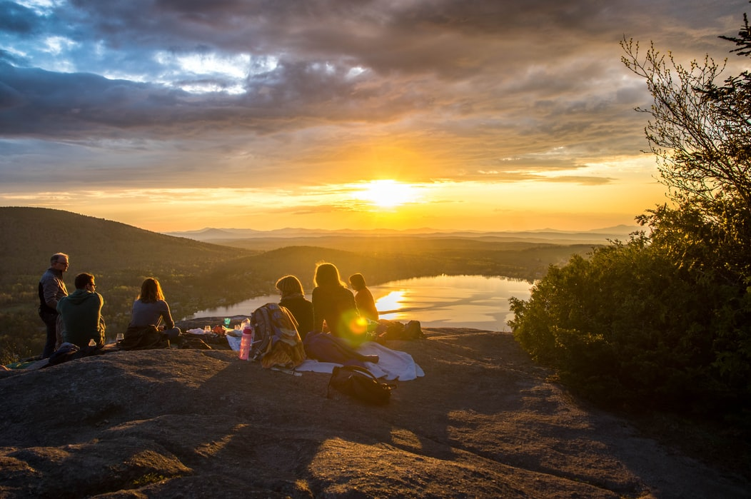 A group of people camping and looking at the sunset