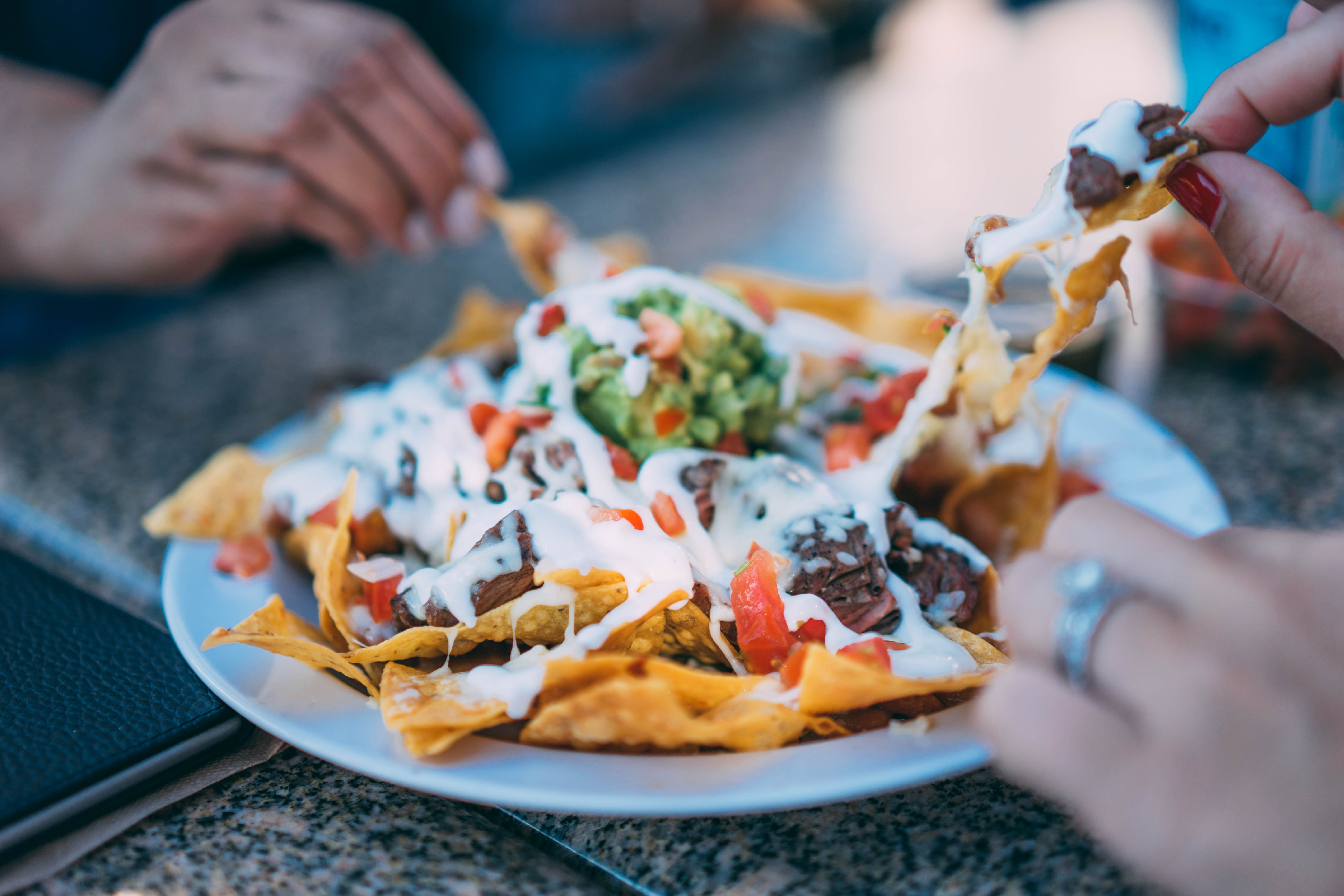 People sharing a plate of Mexican nachos with vegetables and meat
