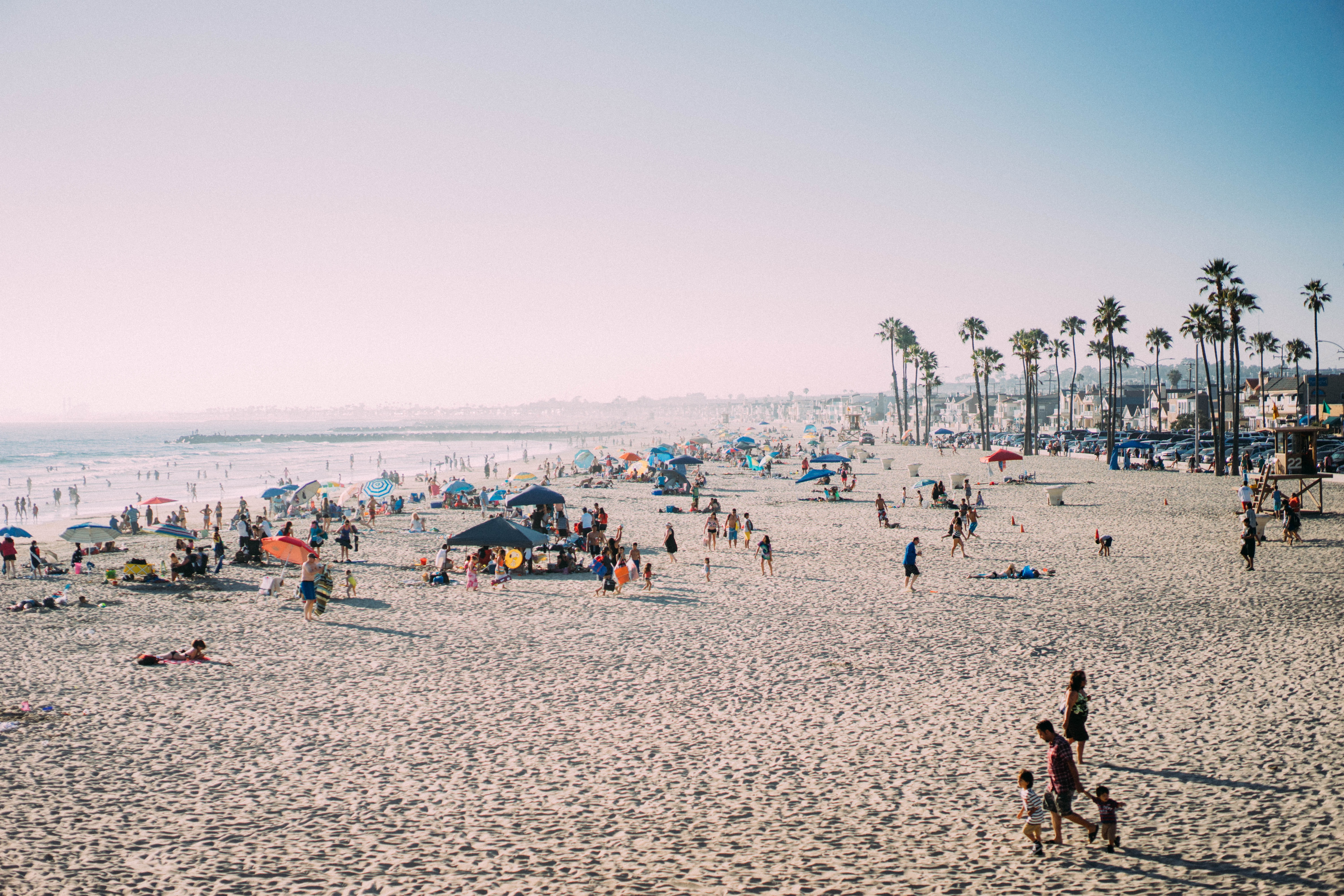 People enjoying the tropical sun, sea, and sand at a fairly crowded Newport Beach, CA