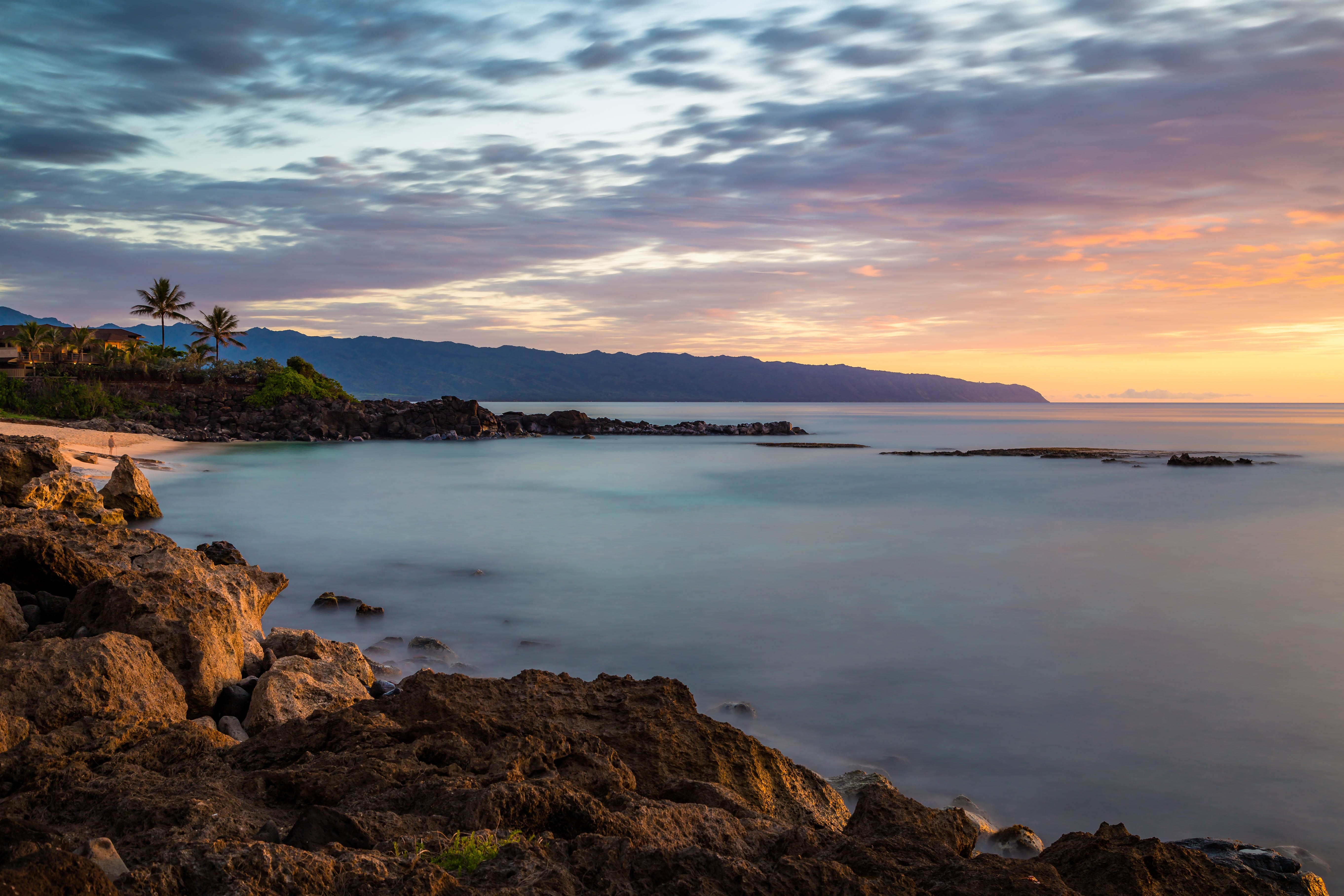 Rocky shoreline with palm trees by the calm ocean at Three Tables Beach during sunset
