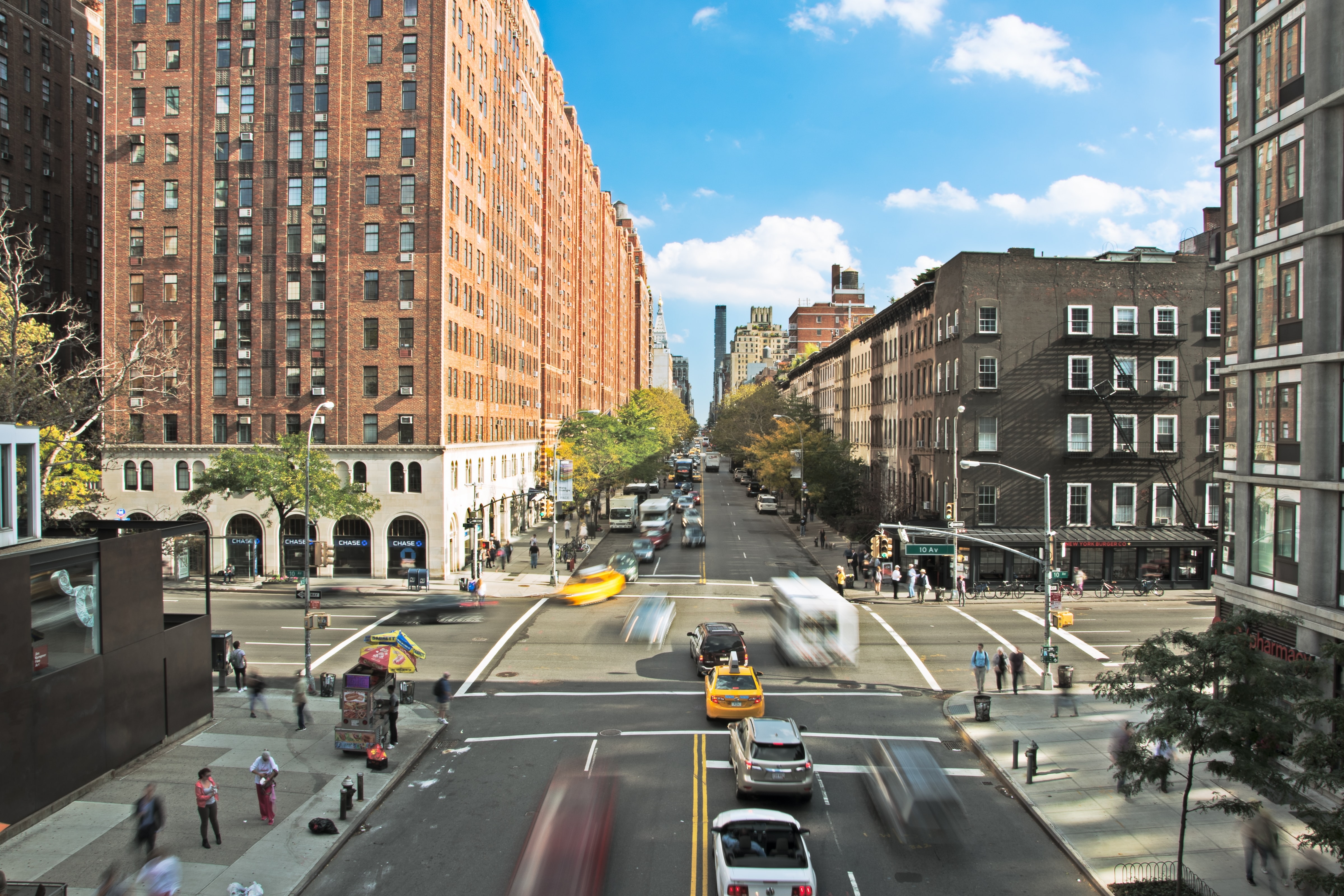 New York City intersection with taxis, cars, and buses driving and people walking