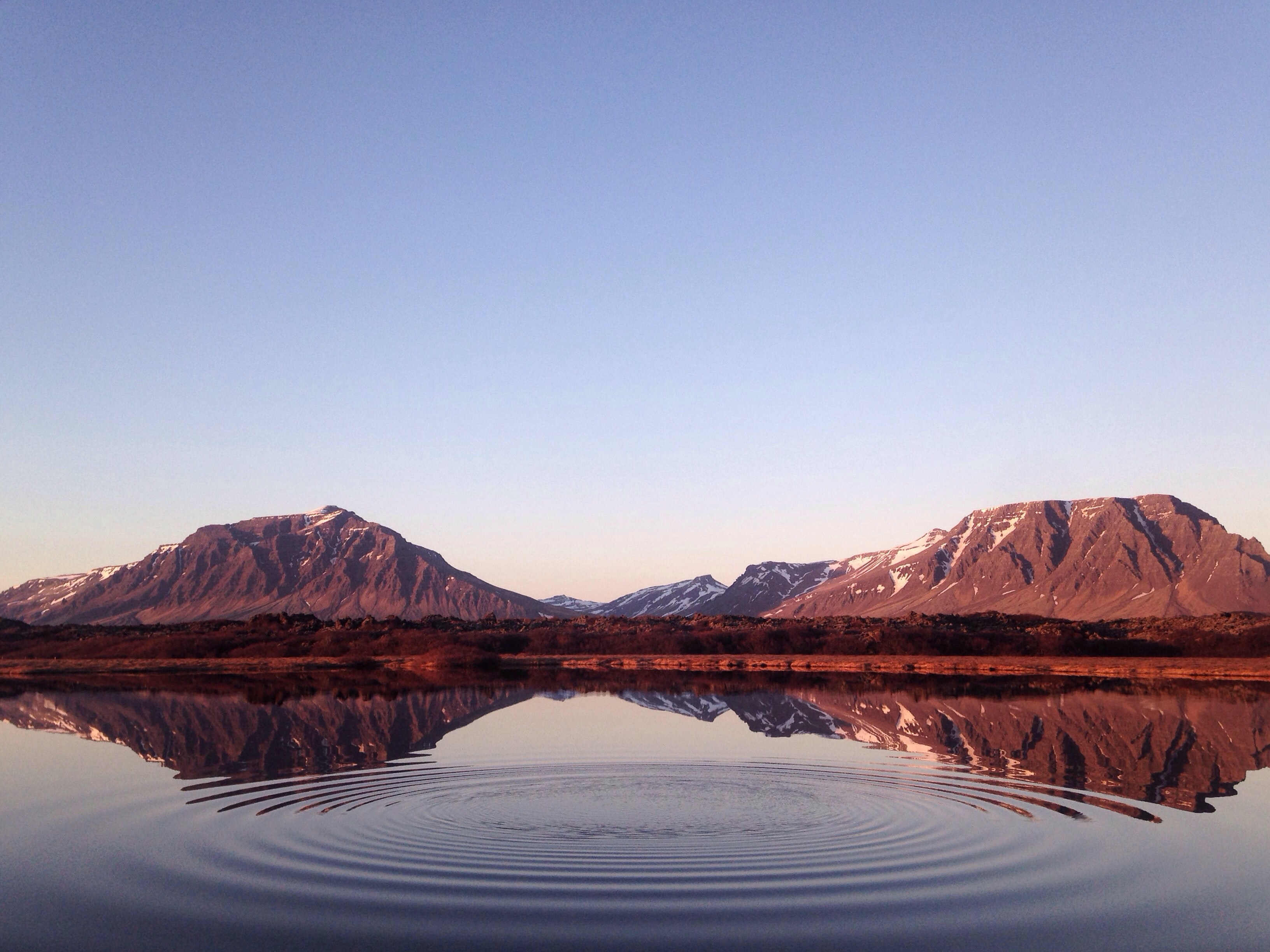 A ripple in the still surface of a lake with flat mountains on the distant shore