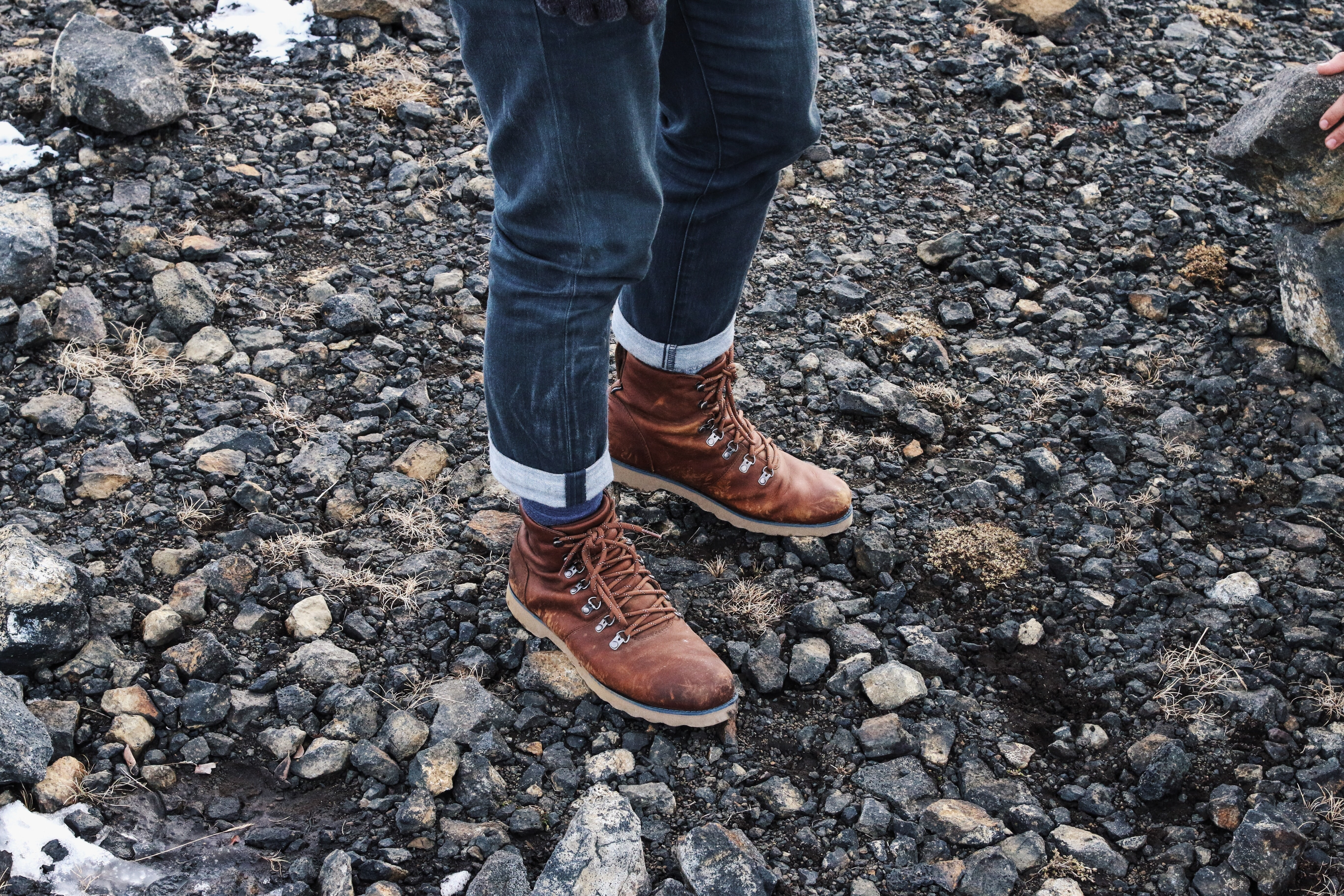 A person standing on a gravel surface wearing brown boots and blue jeans