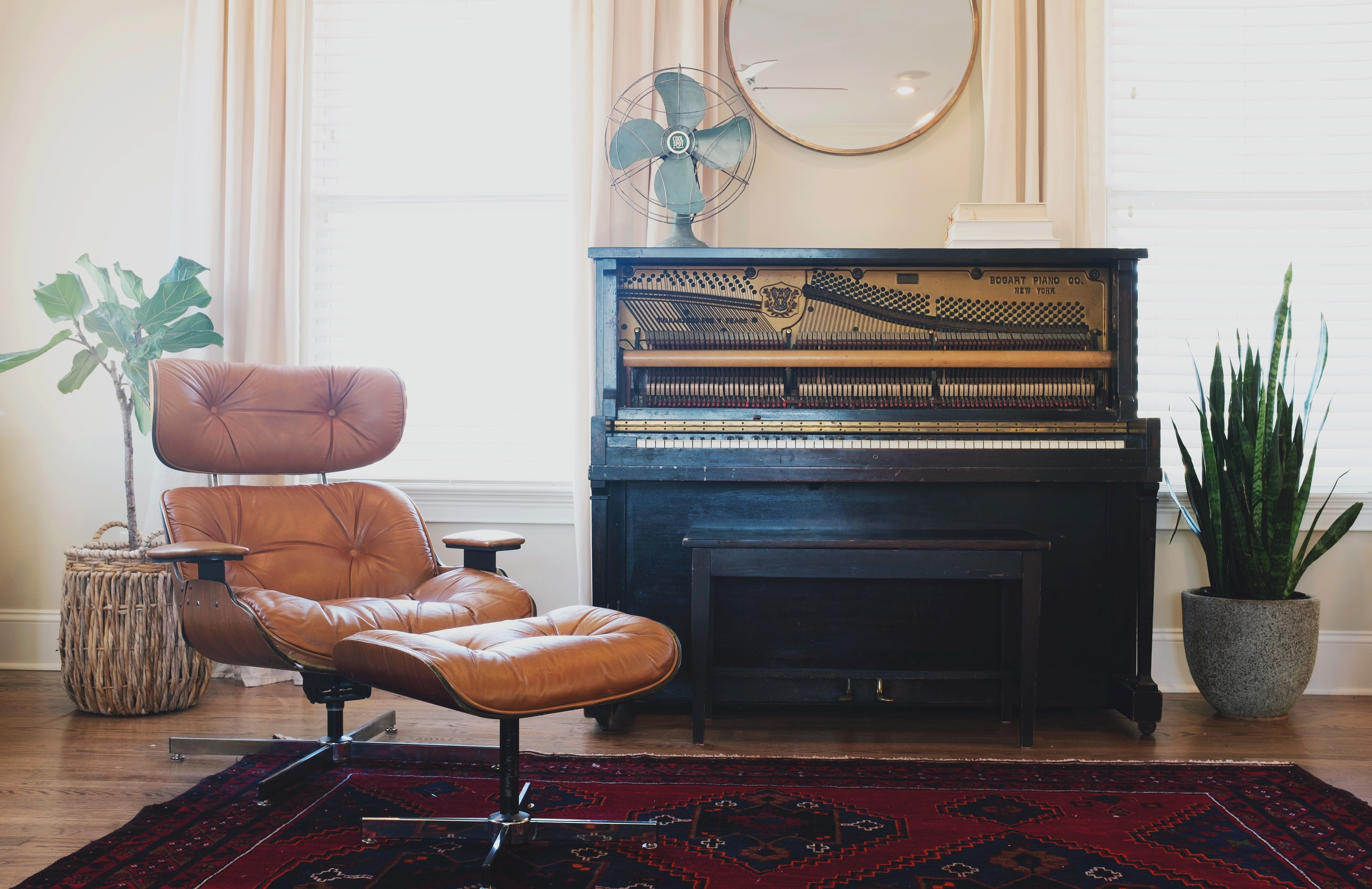 A leather chair with a footstool next to a piano with an exposed soundboard