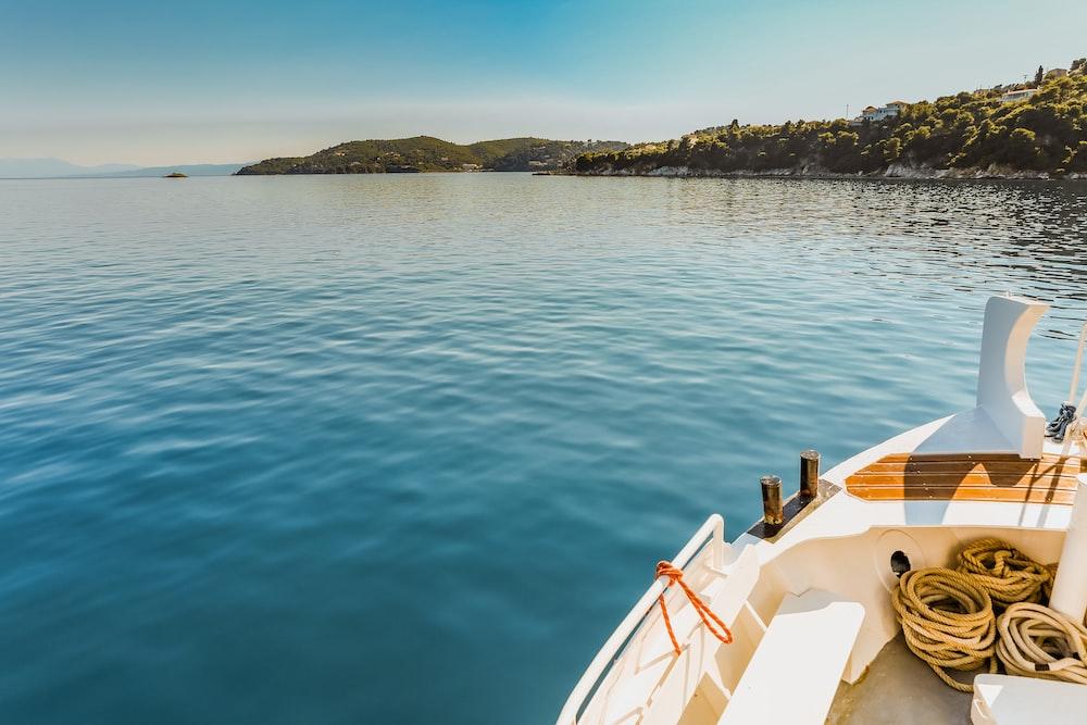 white canoe docked on calm water near island