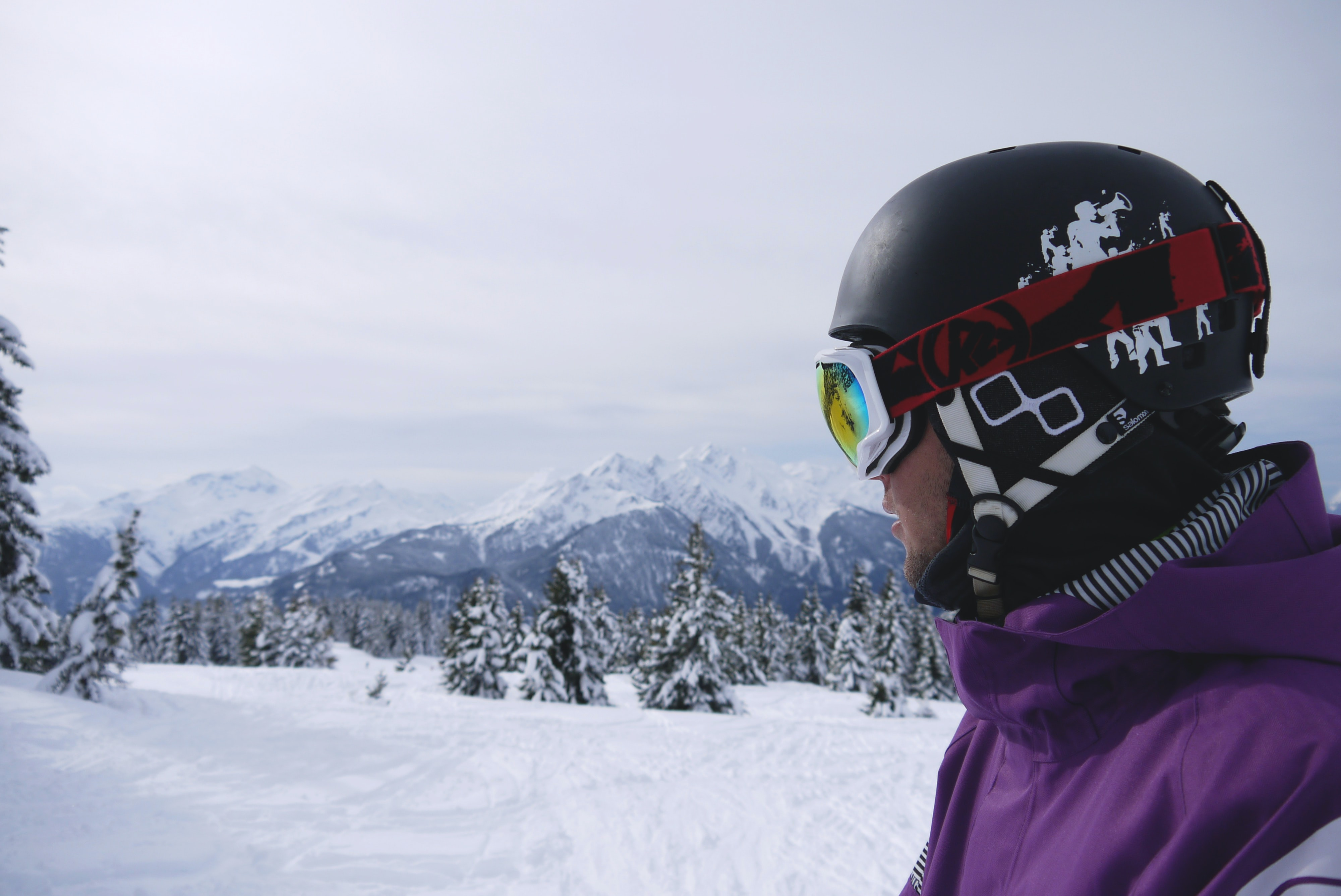 man wearing black helmet and snow goggles under white sky