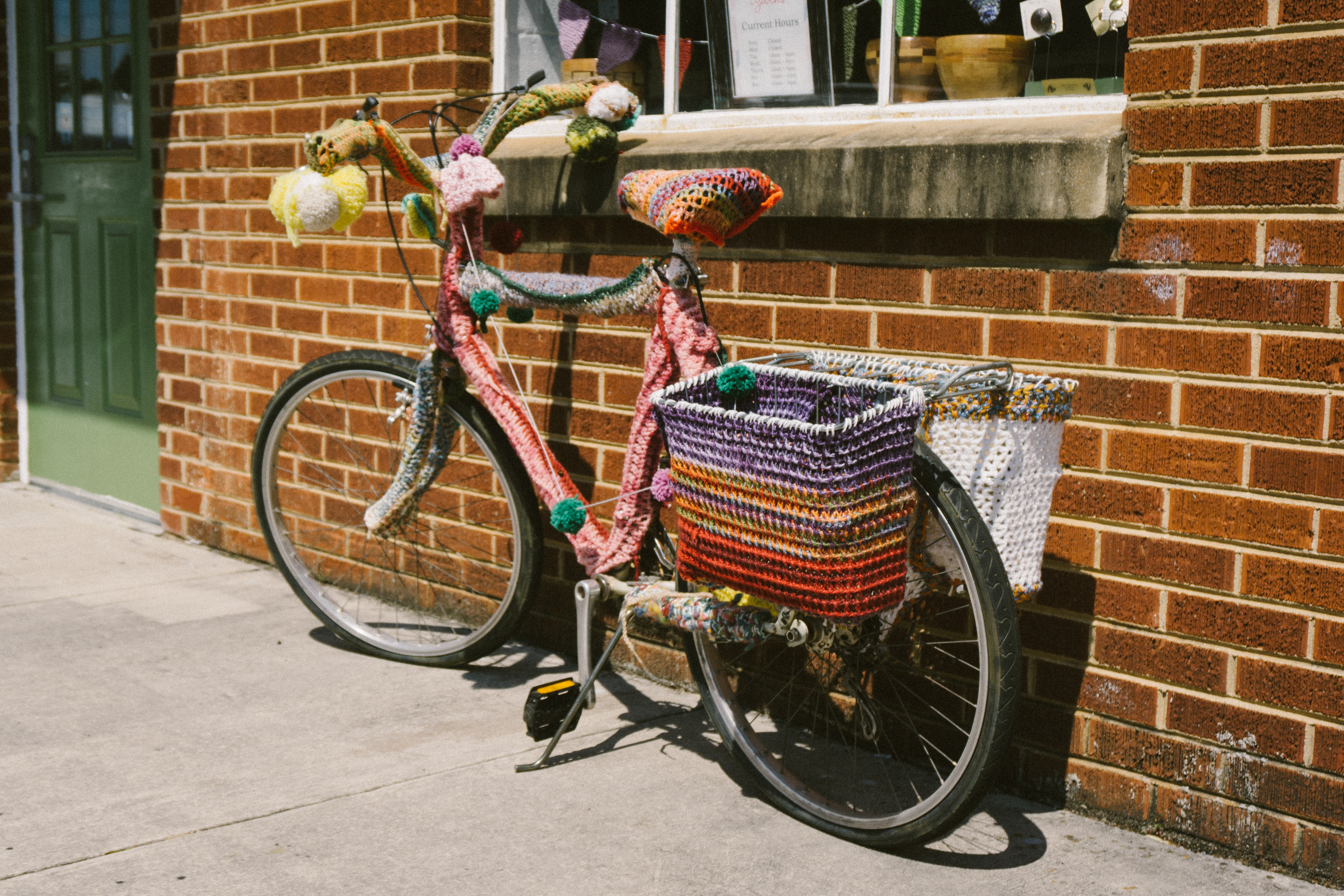 A parked bicycle with colorful crocheted yarn wrapped around its handlebars, seat, and frame