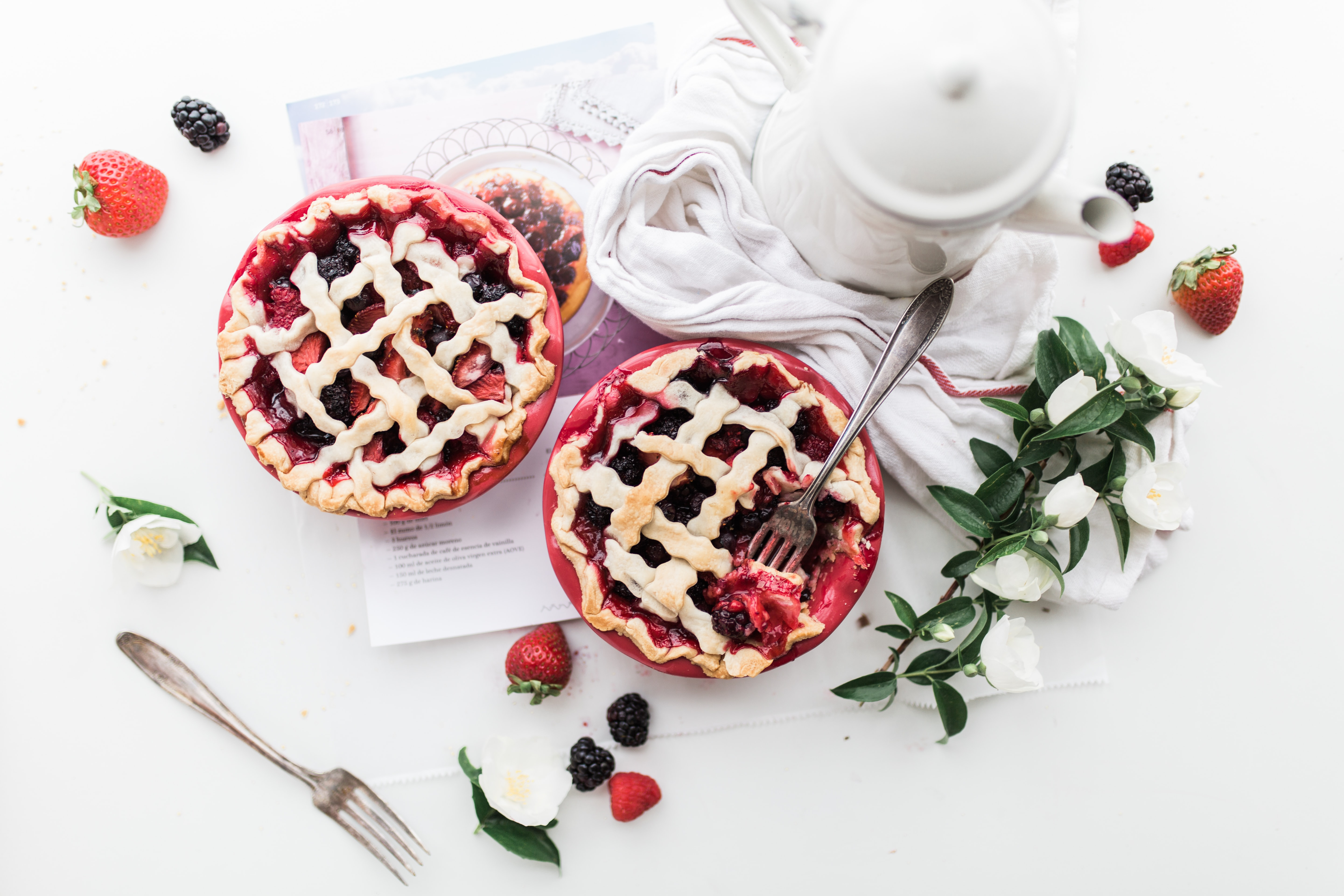 An overhead shot of strawberry and blackberry pies next to a white coffee pot and a bunch of flowers