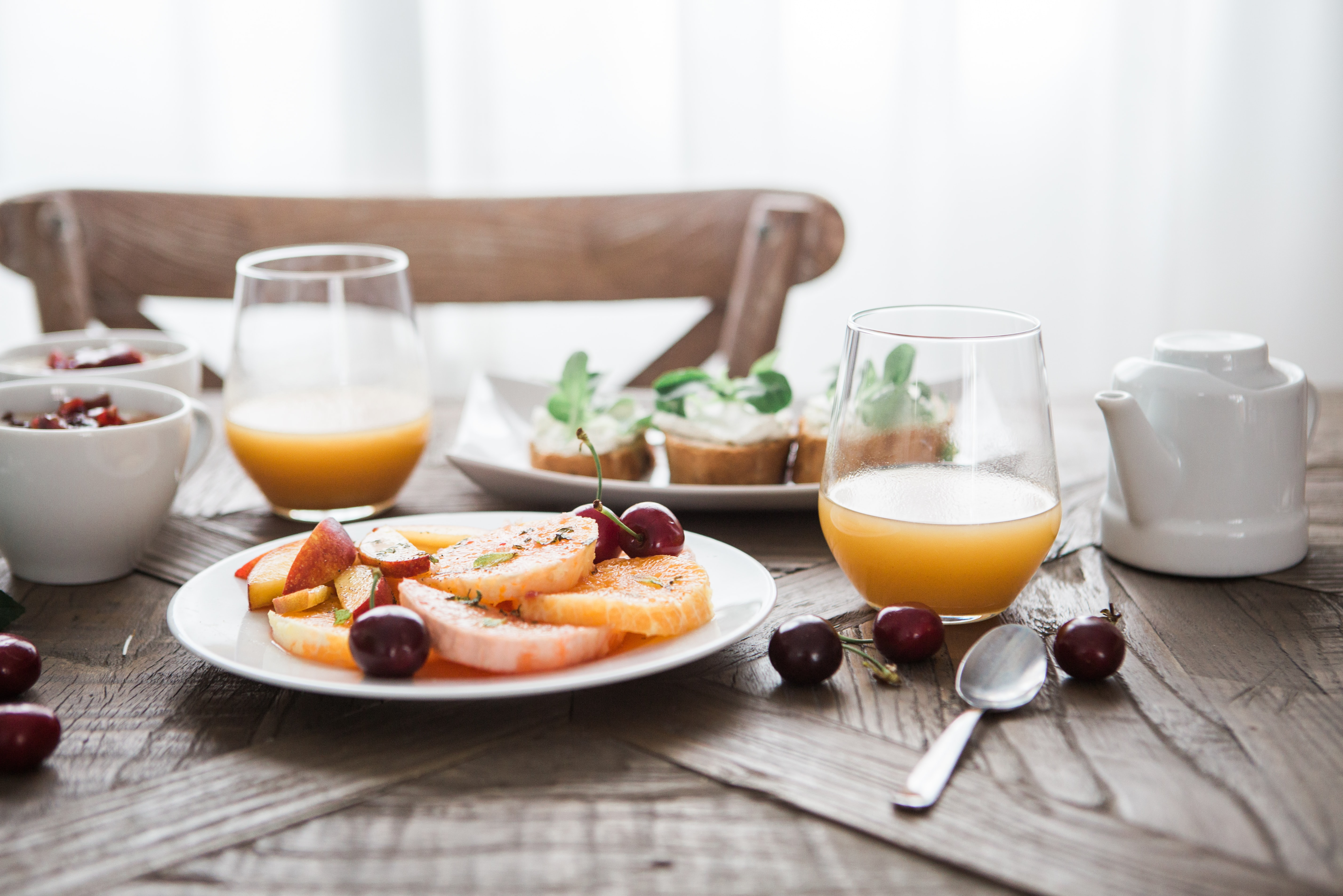 A breakfast with fruits, orange juice and bread with cream on a wooden table