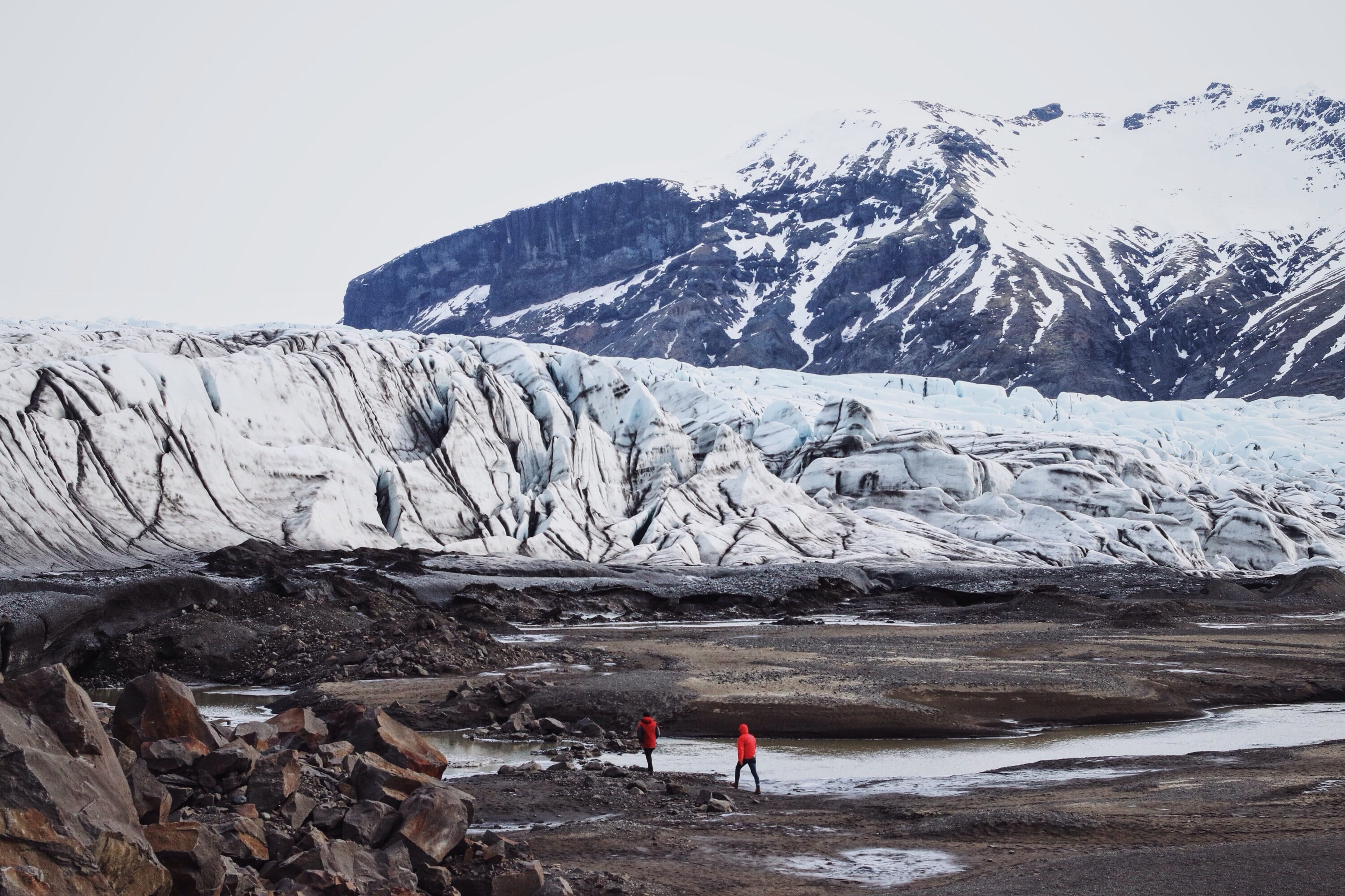 Two people in red jackets walking along a stream flowing under a mountain glacier