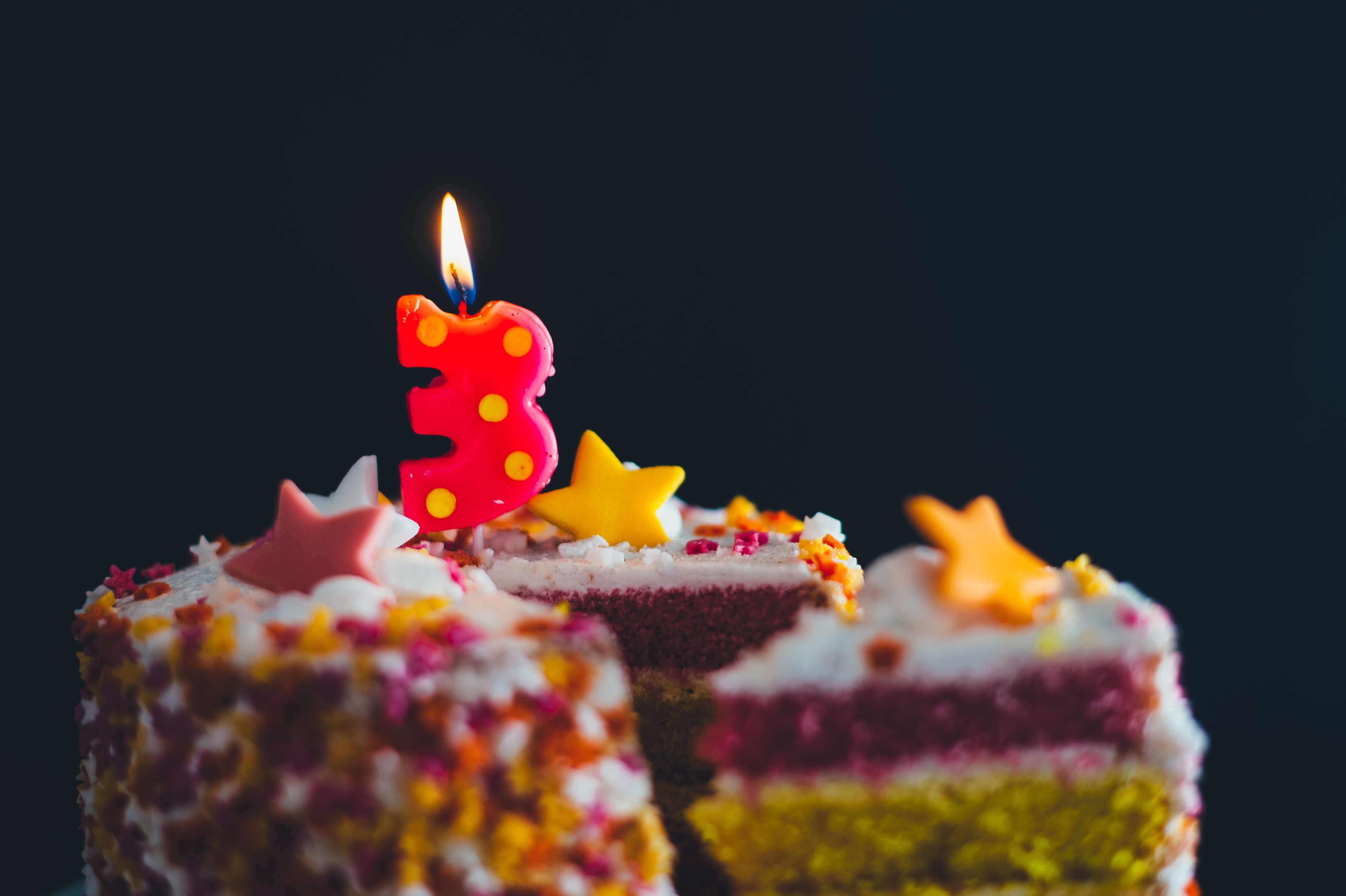 A close-up macro shot of a sliced birthday cake with a number 3 candle burning on top