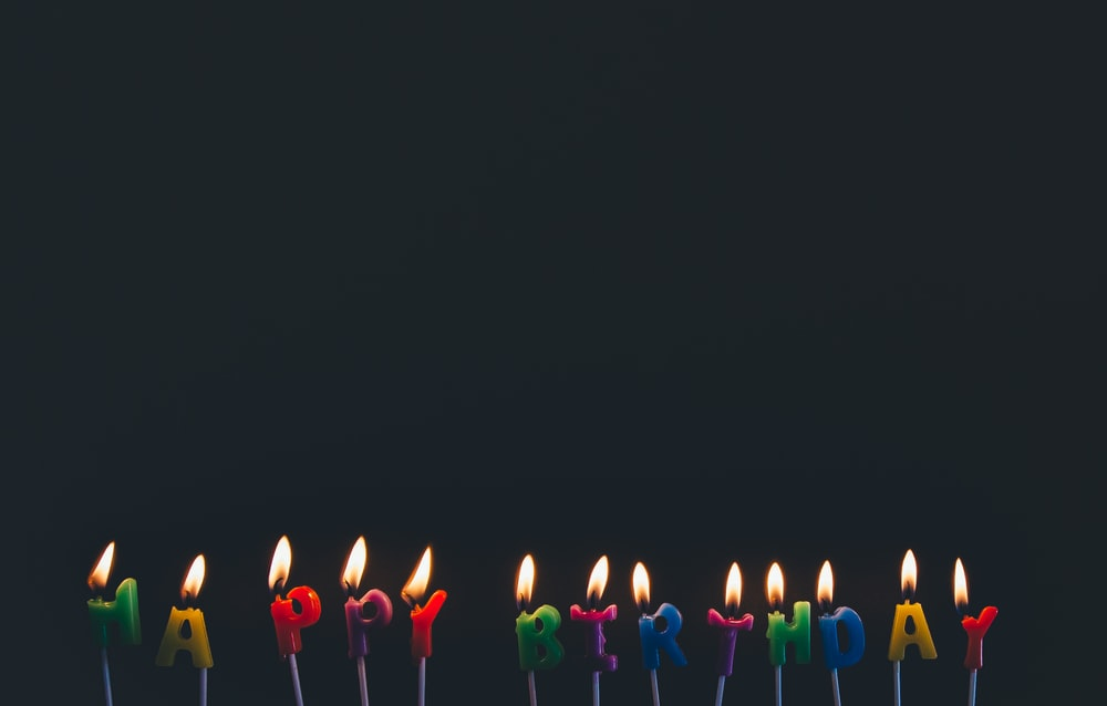 assorted-color Happy Birthday candles with flames