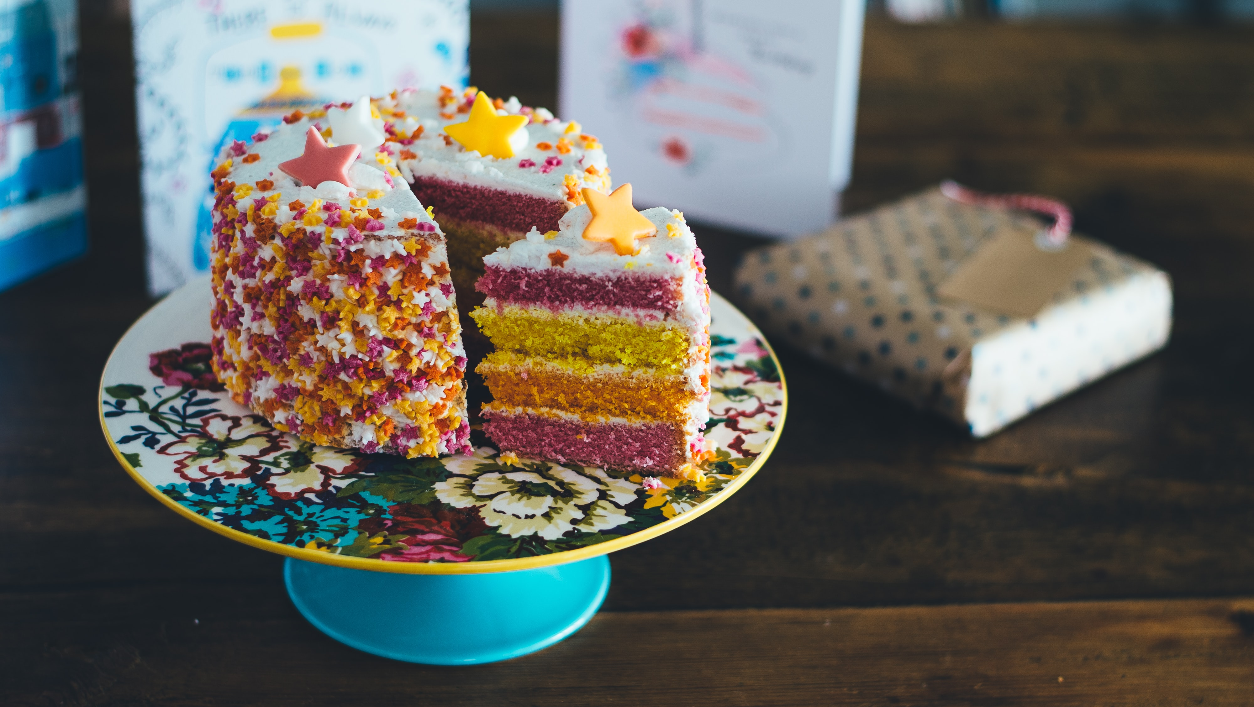 A birthday cake with rainbow sponge and stars on top, with a slice cut out and sat at an angle on the plate