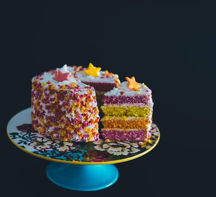 Colorful cake topped with stars, on a cake plate with flowery design.