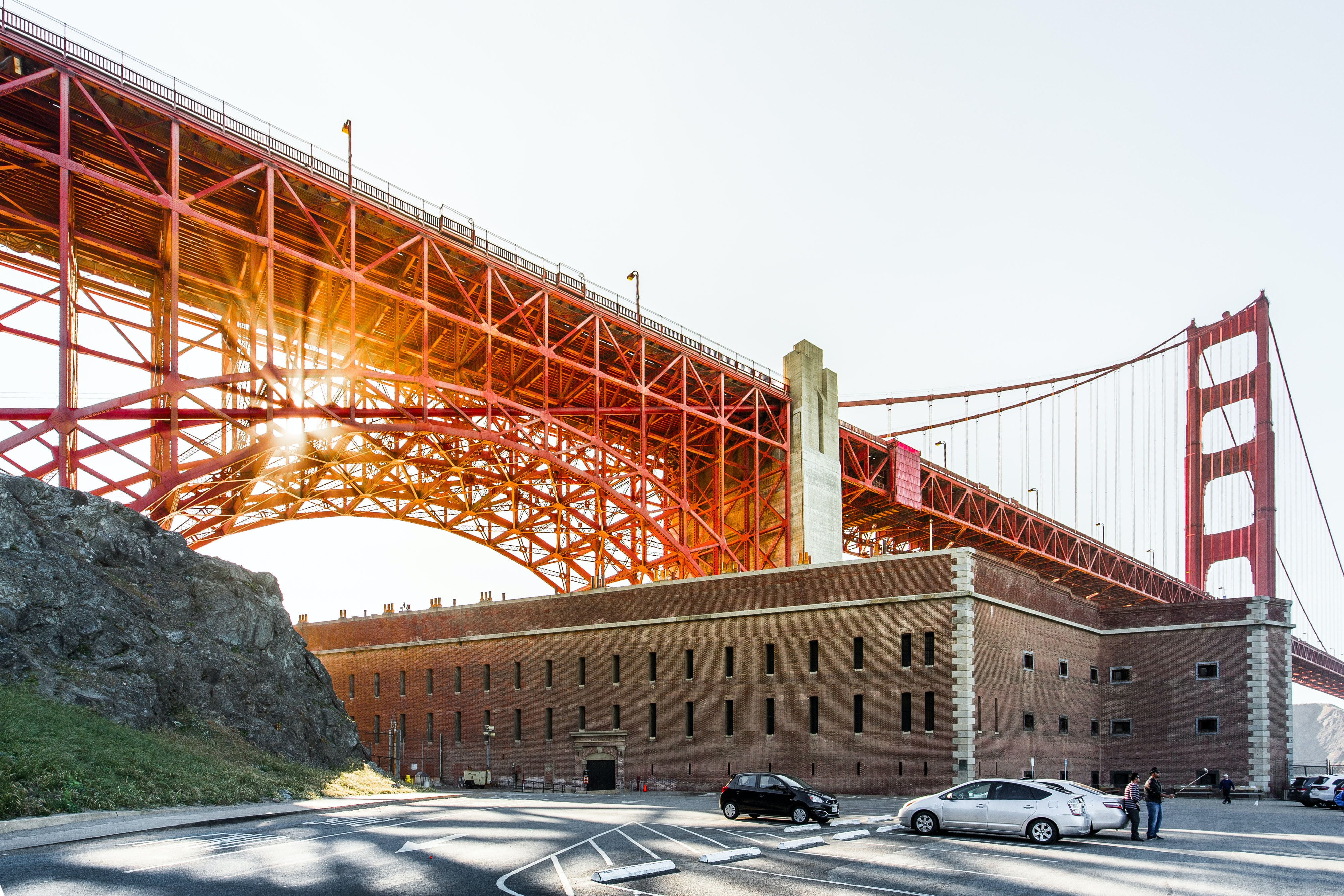 San Francisco Golden Gate Bridge at sunset suspended over a brown building, cars and people
