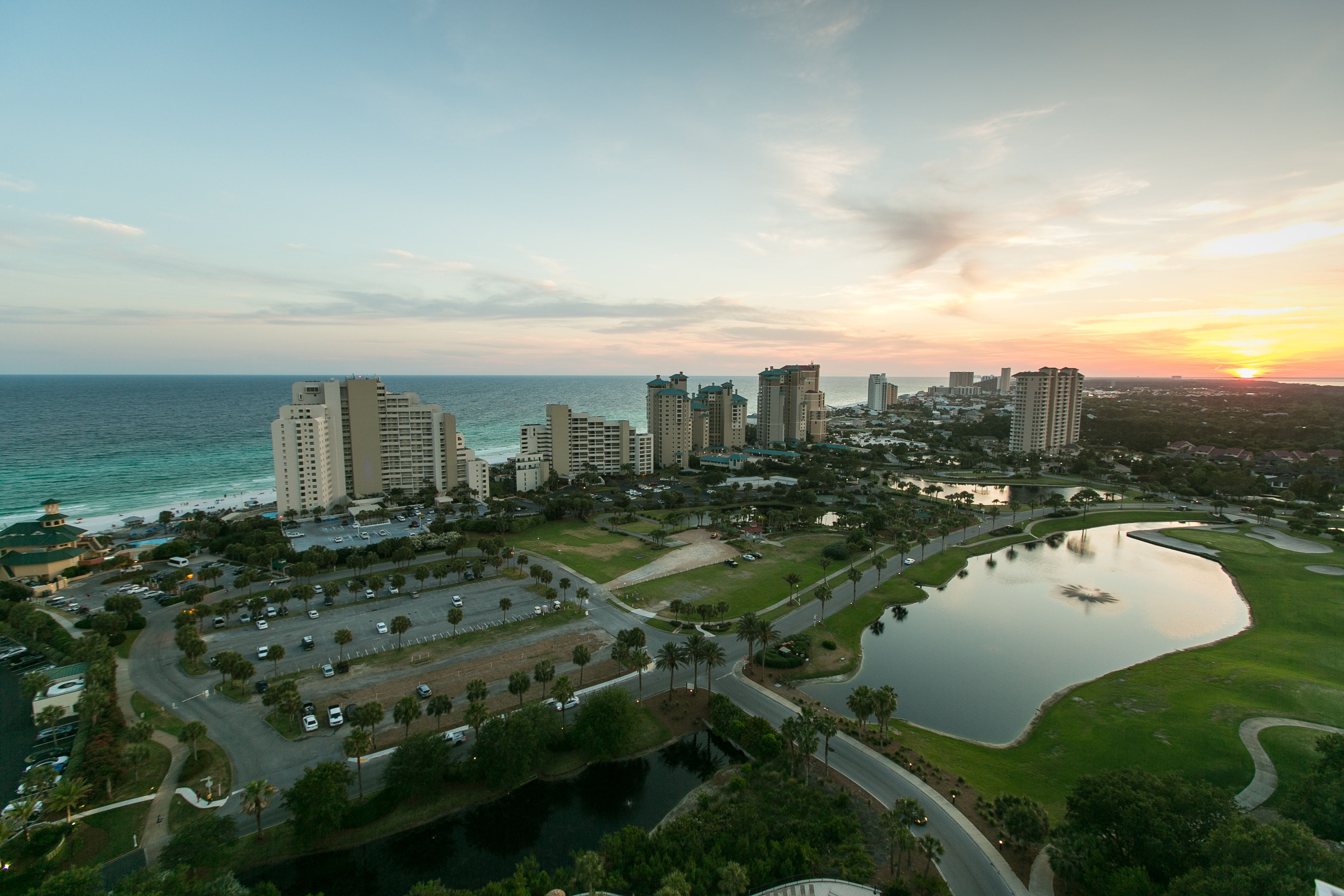 Drone shot of skyscrapers, blue lake, parking lot and palm trees in Destin at sunset