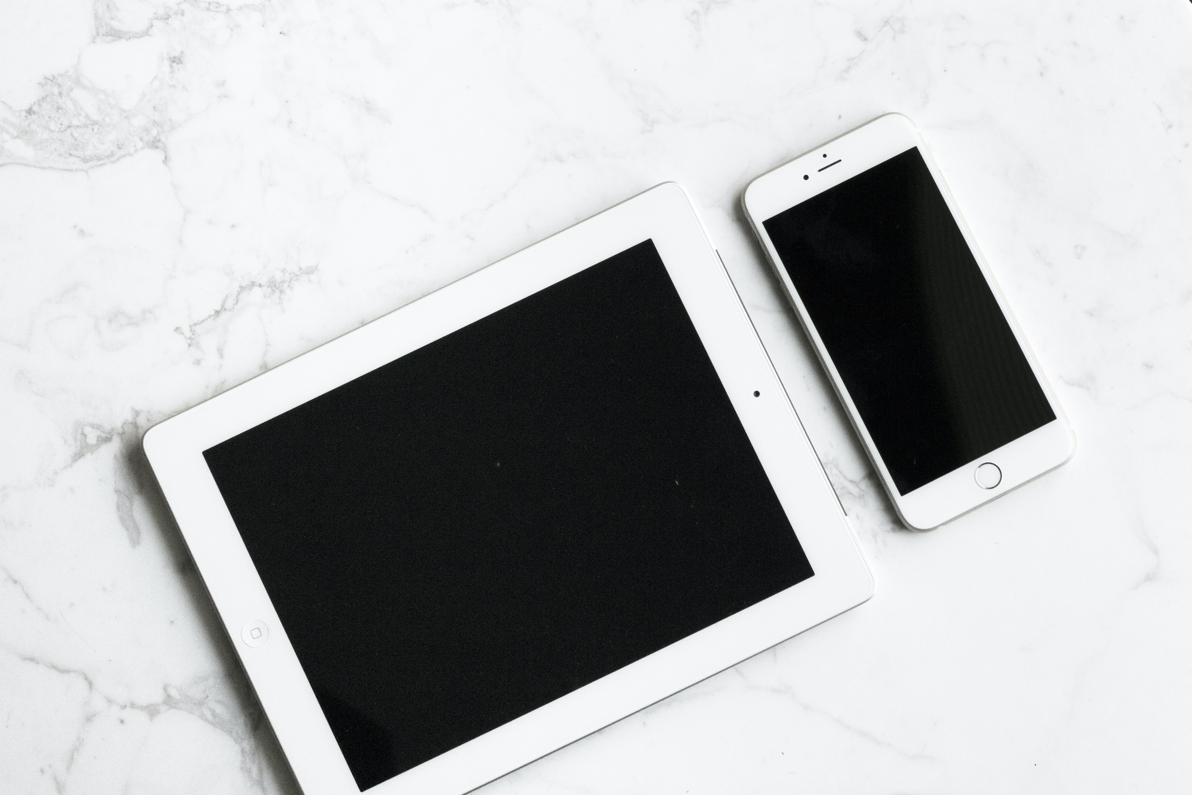An overhead shot of an iPad next to an iPhone on white marble surface