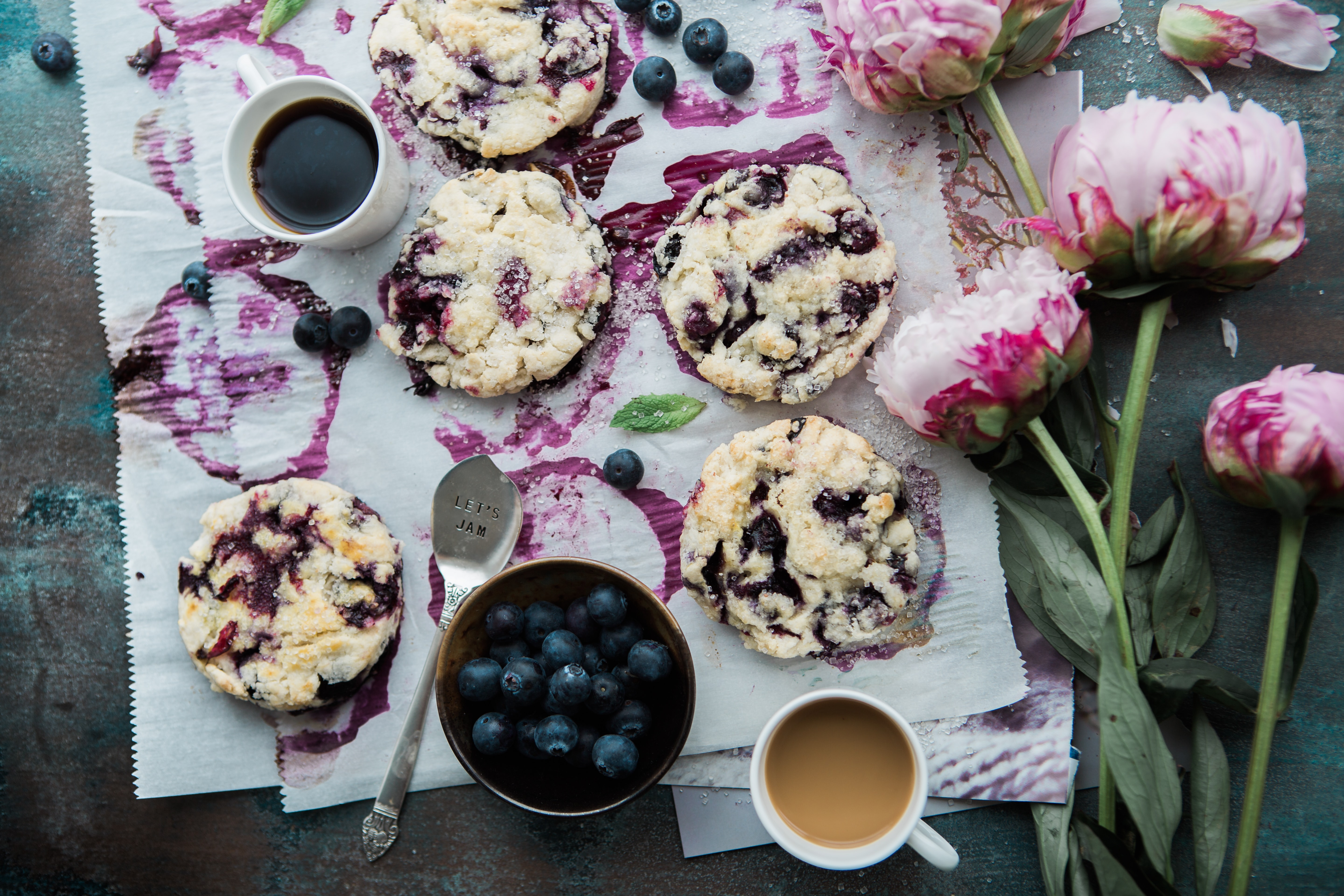 An overhead shot of blueberry scones with coffee and pink flowers laid out on the side