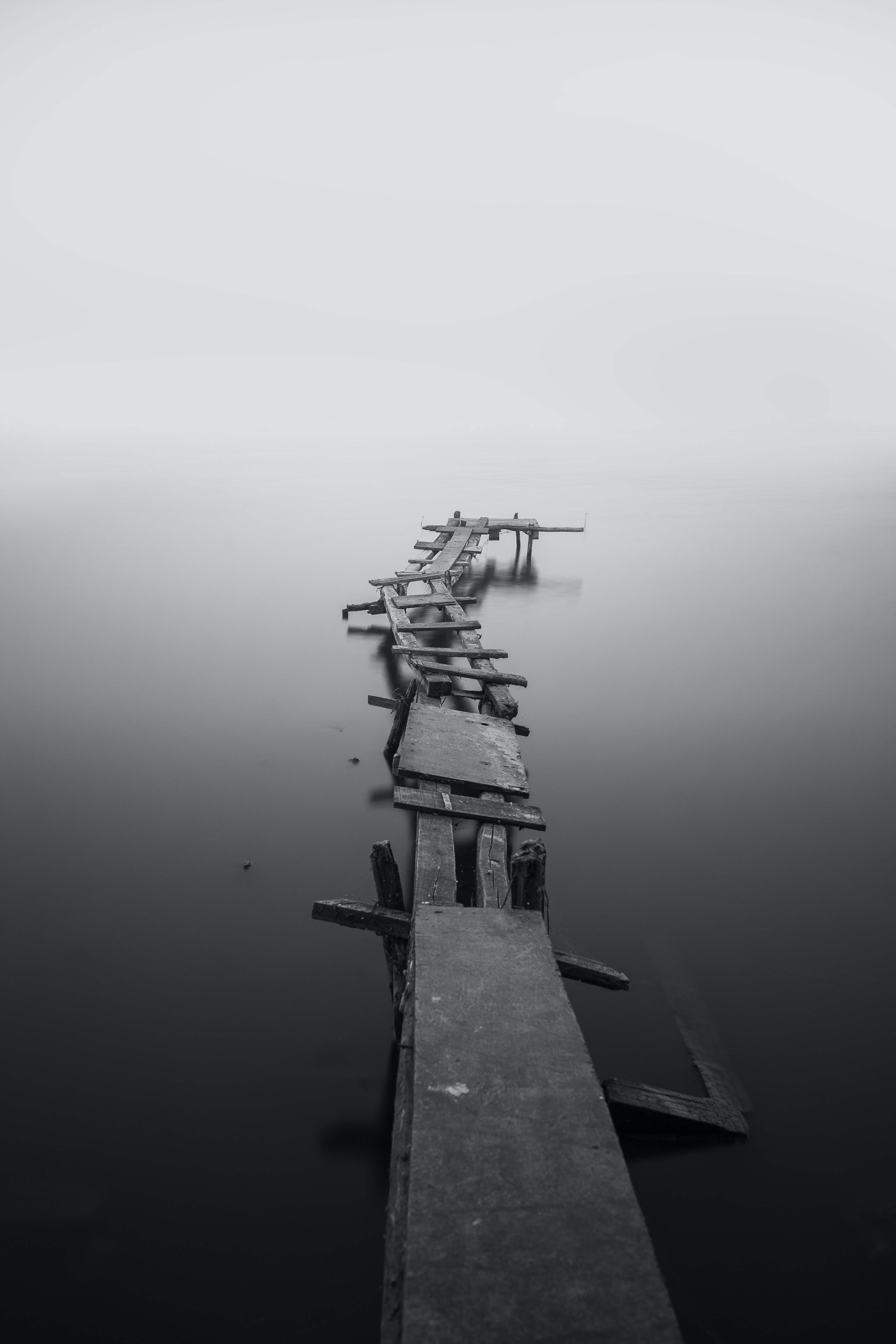Black and white shot of crooked jetty in lake water with mist
