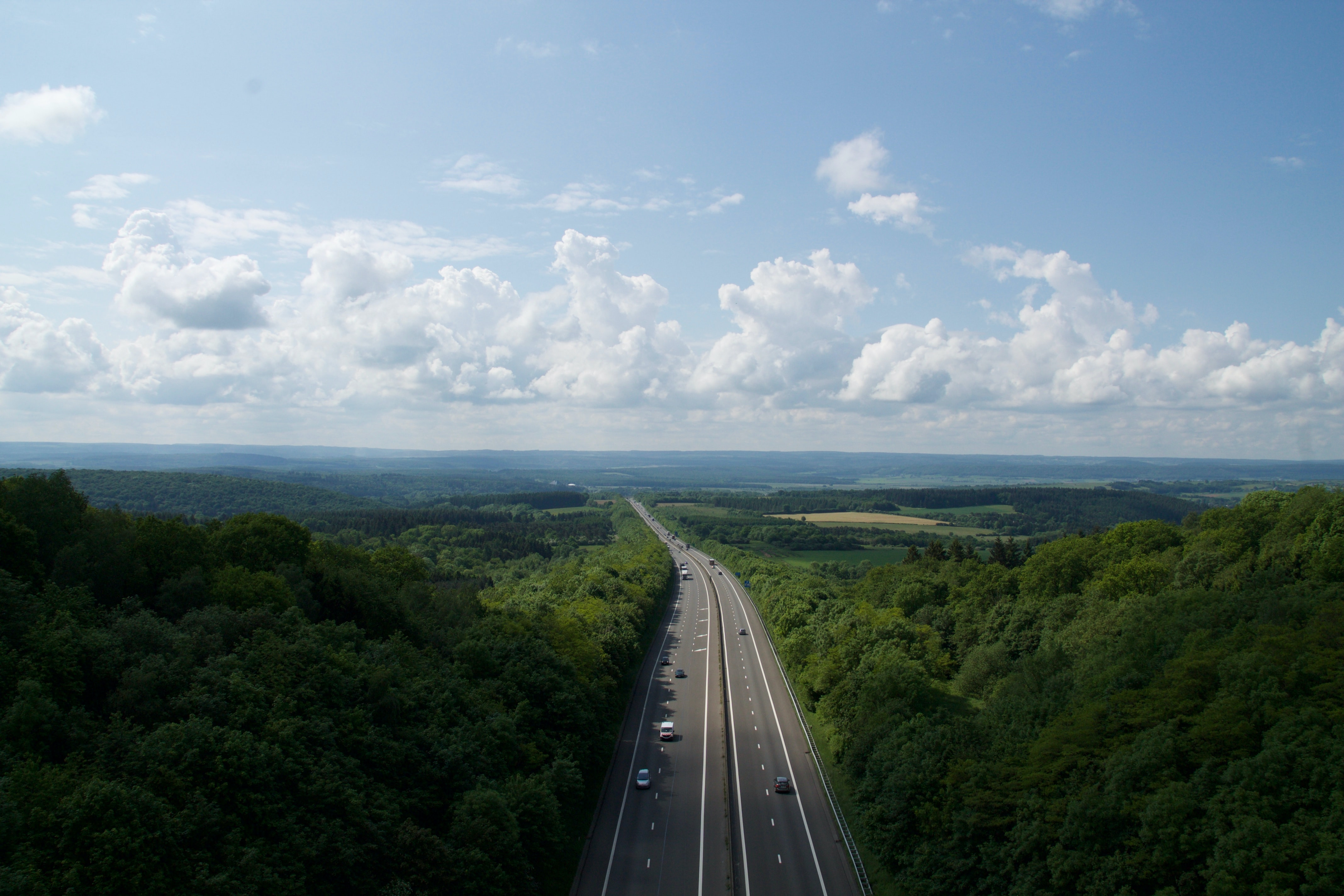 Aerial drone shot of a countryside highway on a bright blue day