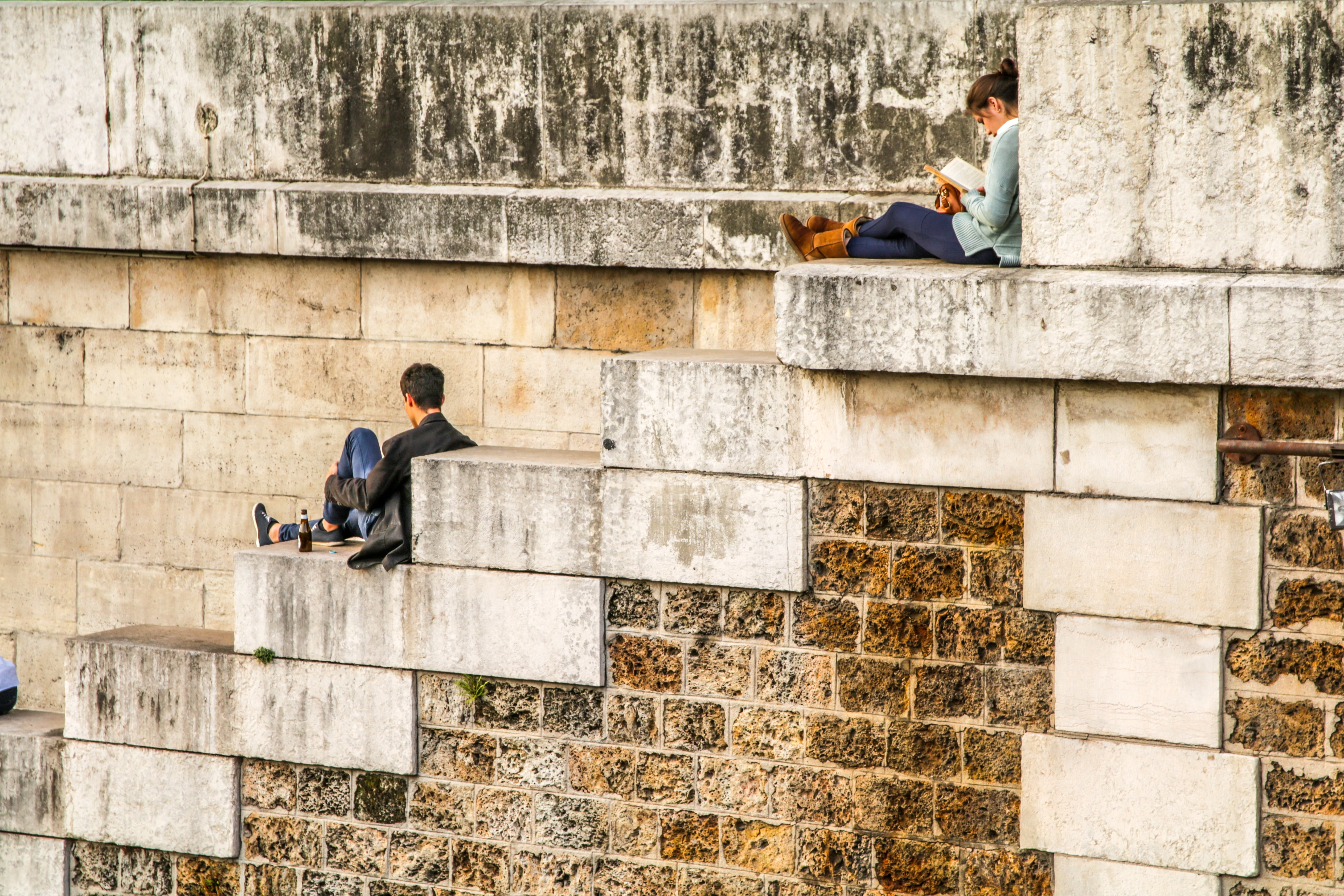 A woman reading a book on brick an stone stairs while a man drinks a beverage.