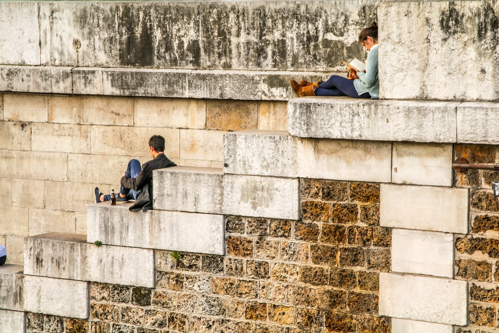 man sitting on staircase behind woman sitting on highest staircase