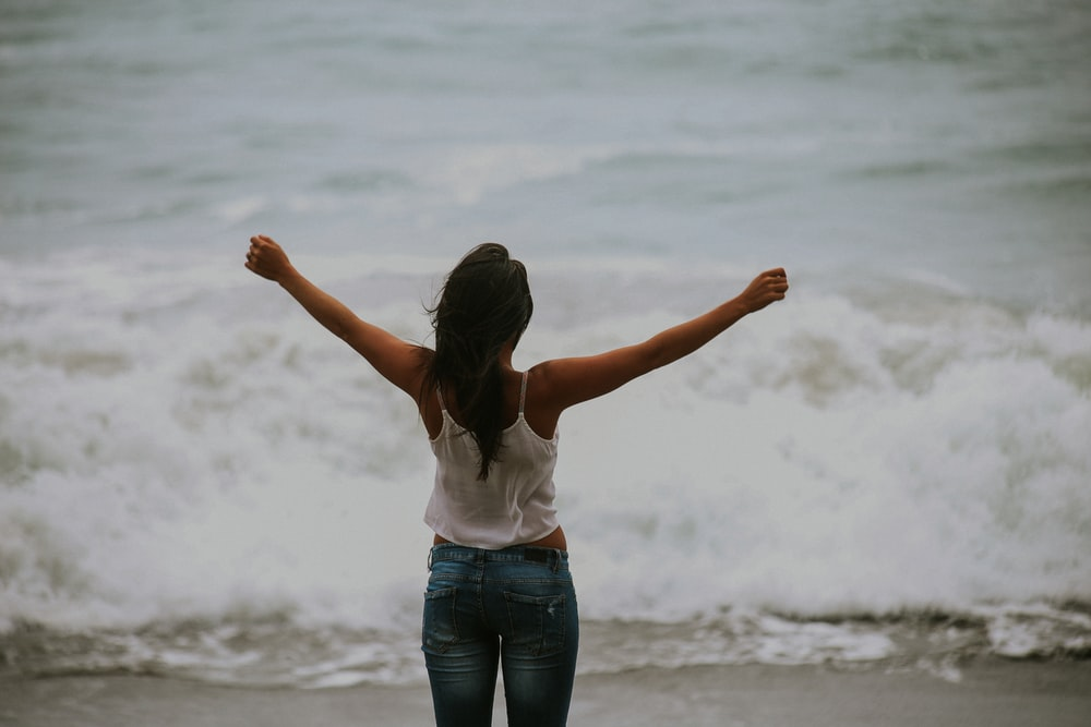 A woman wearing jeans and a white shirt staring out at the ocean with her arms up at Bodega Bay