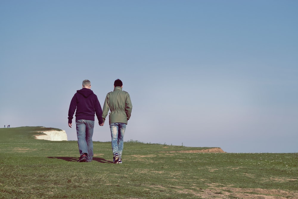two person walking on green grass field