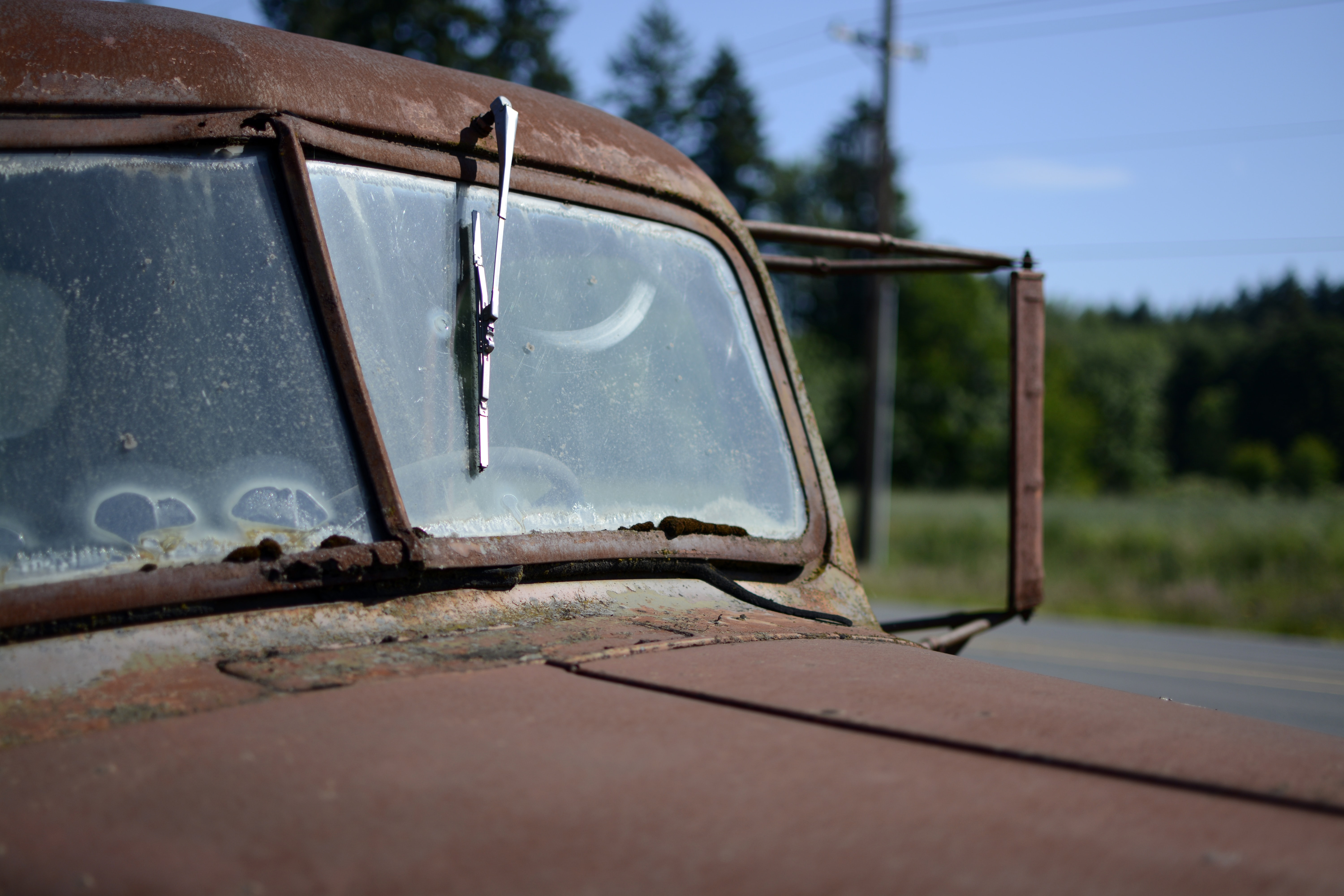 Windshield and broken window wiper of a rusty, burgundy truck in Sherwood during daylight