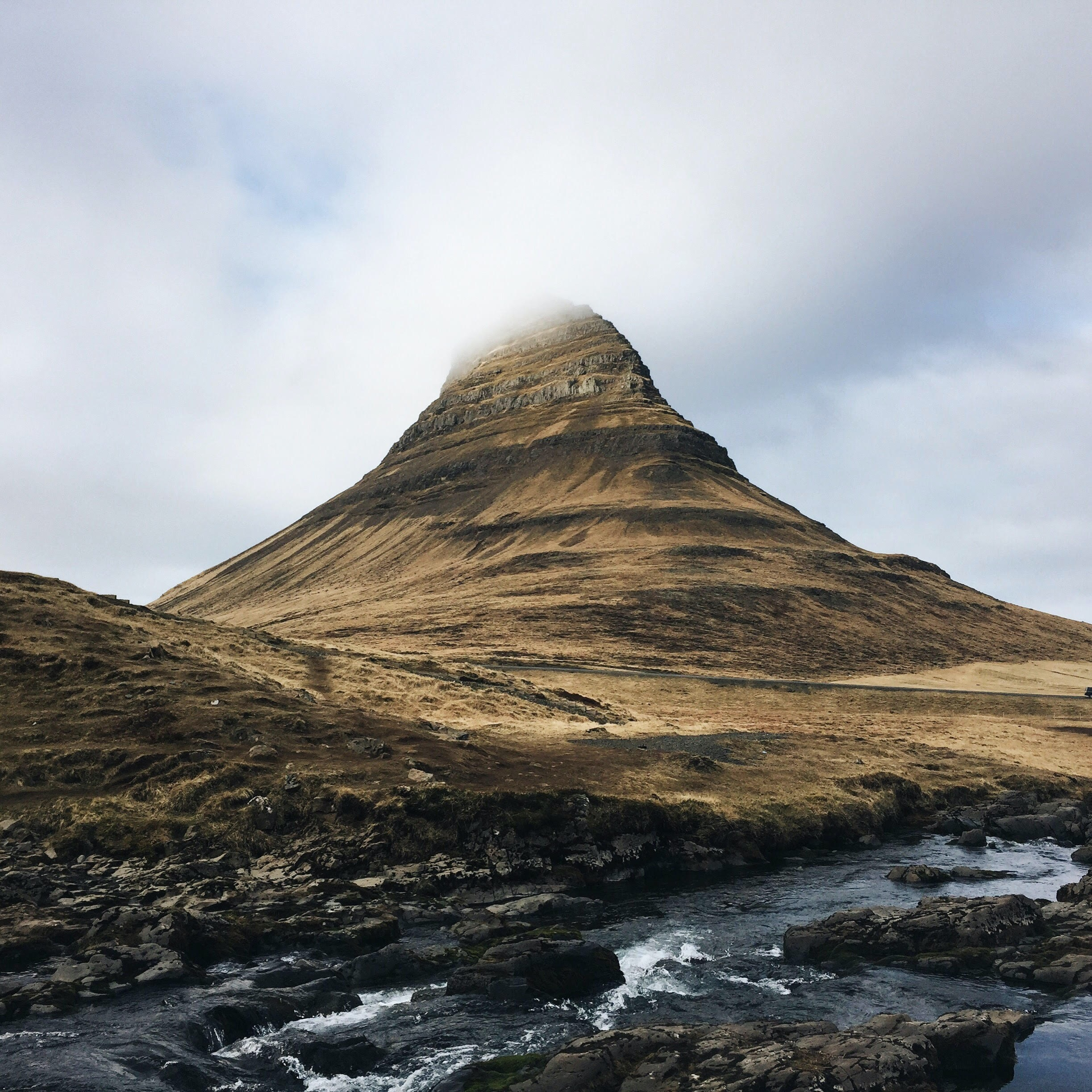 Mountain in Kirkjufell disappears into the cloudy sky
