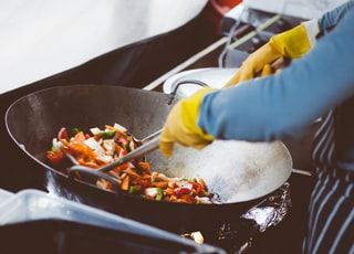 person mixing vegetable in wok