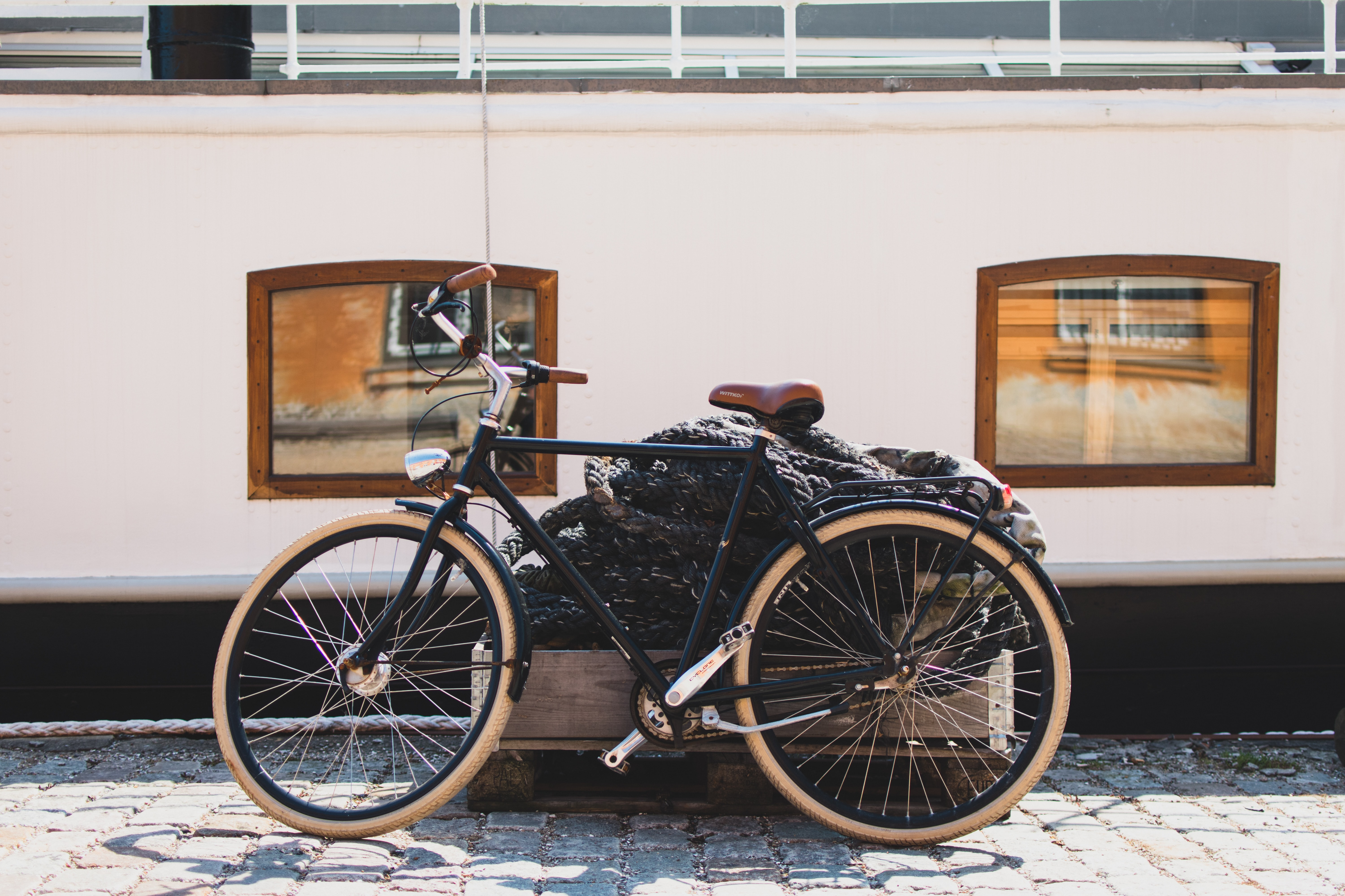 Bicycle on a cobblestone street in Copehagen in front of rope and two windows